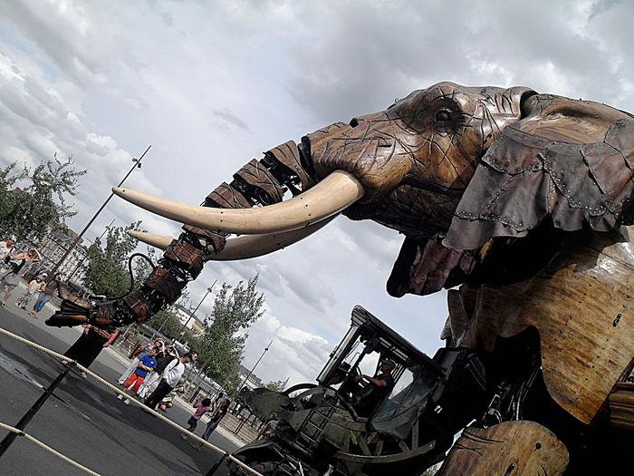 Machine Wood Animal Representation Automaton Cloud - Sky Day Elephant Low Angle View Outdoors People Sky Street