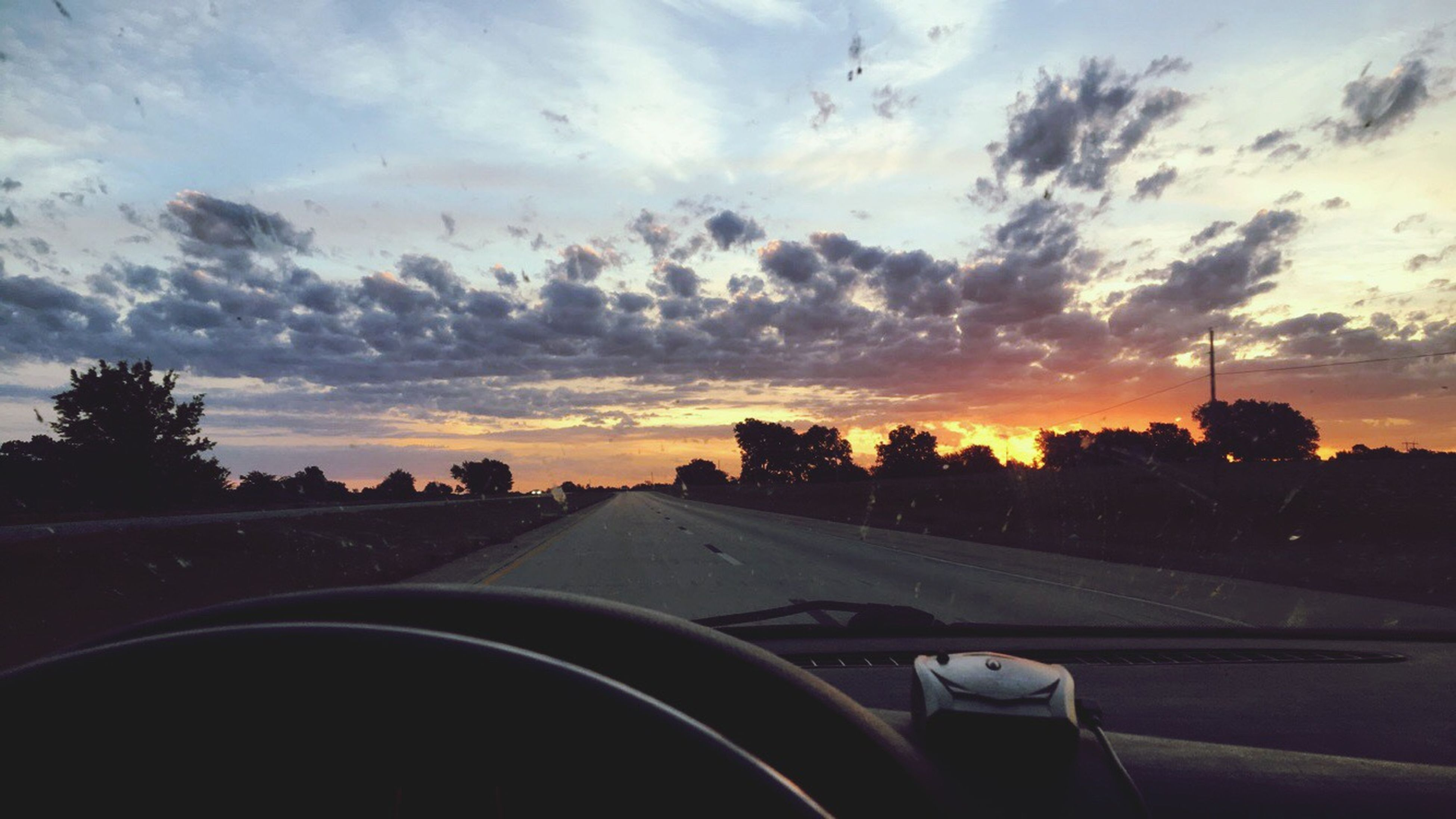 transportation, car, mode of transport, land vehicle, road, sky, windshield, sunset, tree, the way forward, road marking, cloud - sky, car interior, vehicle interior, travel, silhouette, diminishing perspective, on the move, car point of view, street