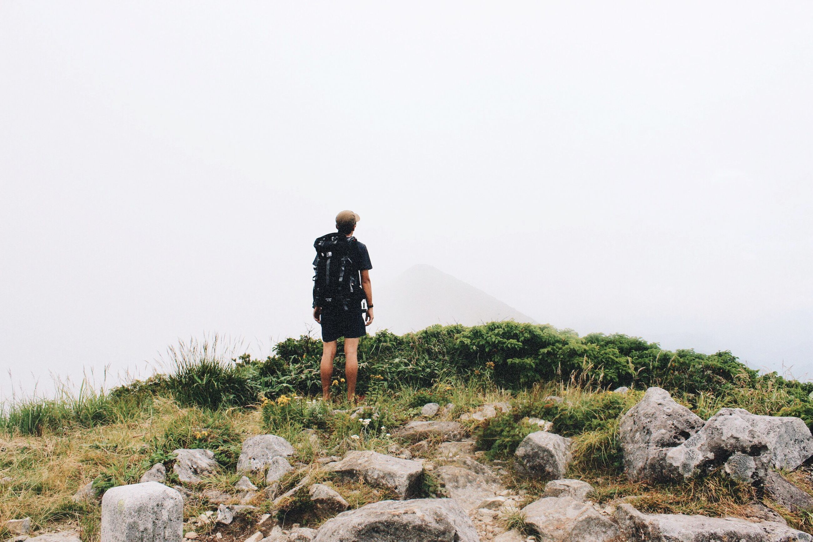 lifestyles, full length, leisure activity, rear view, standing, clear sky, casual clothing, copy space, rock - object, tranquility, men, tranquil scene, nature, landscape, beauty in nature, getting away from it all, person, scenics