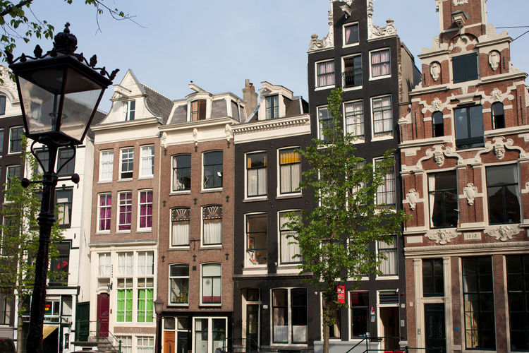 Typical canal-side houses in Amsterdam, Netherlands. Amsterdam Architecture Building Exterior Built Structure Canal Canal-side City Day Dutch House Housing Low Angle View No People Outdoors Residential Building Sky Spring Street Light Window