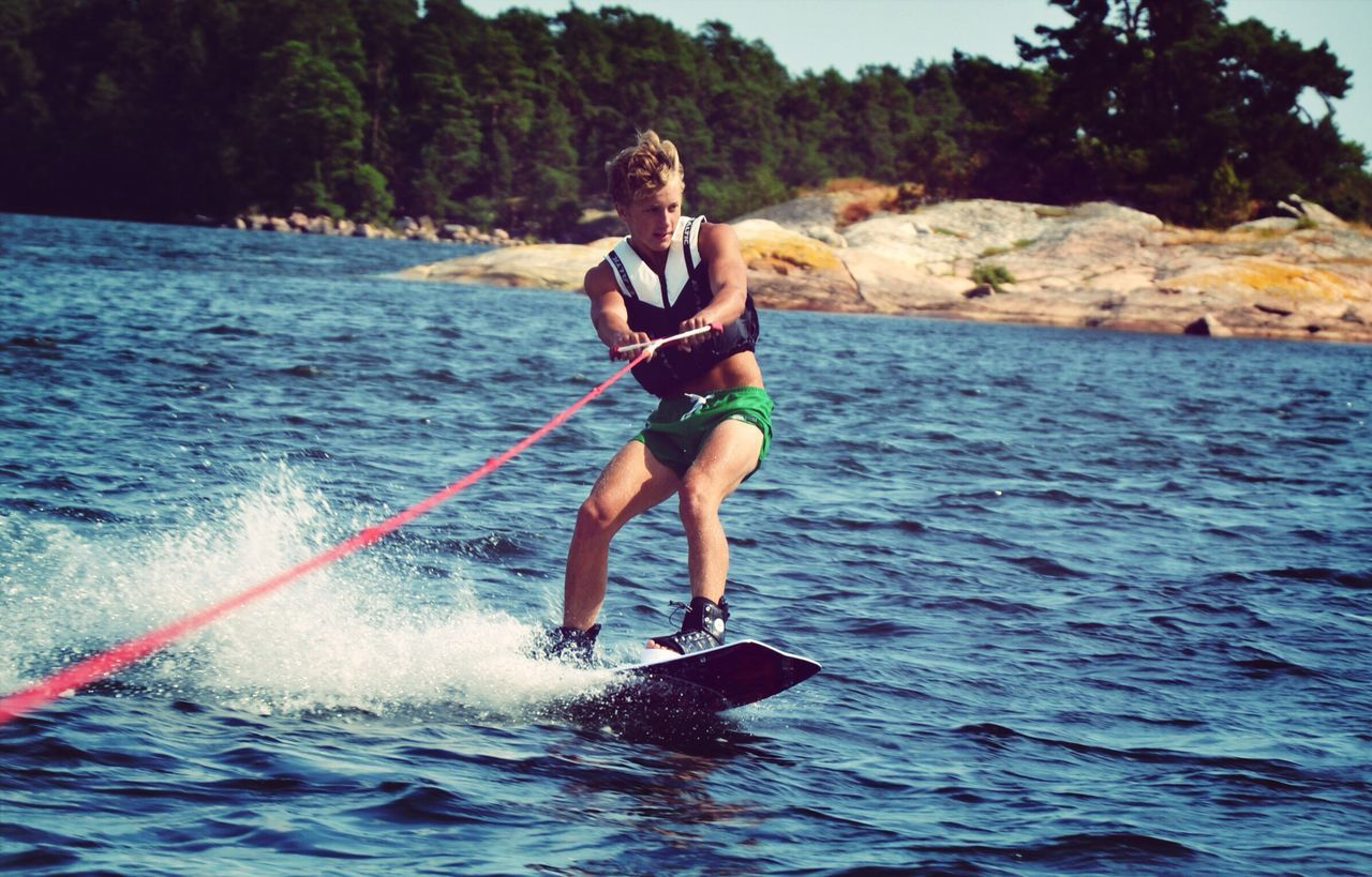 water, one person, real people, full length, leisure activity, oar, nature, day, holding, young adult, outdoors, lifestyles, young men, adventure, sea, looking at camera, standing, paddleboarding, smiling, sitting, beauty in nature, tree, people, adult, adults only