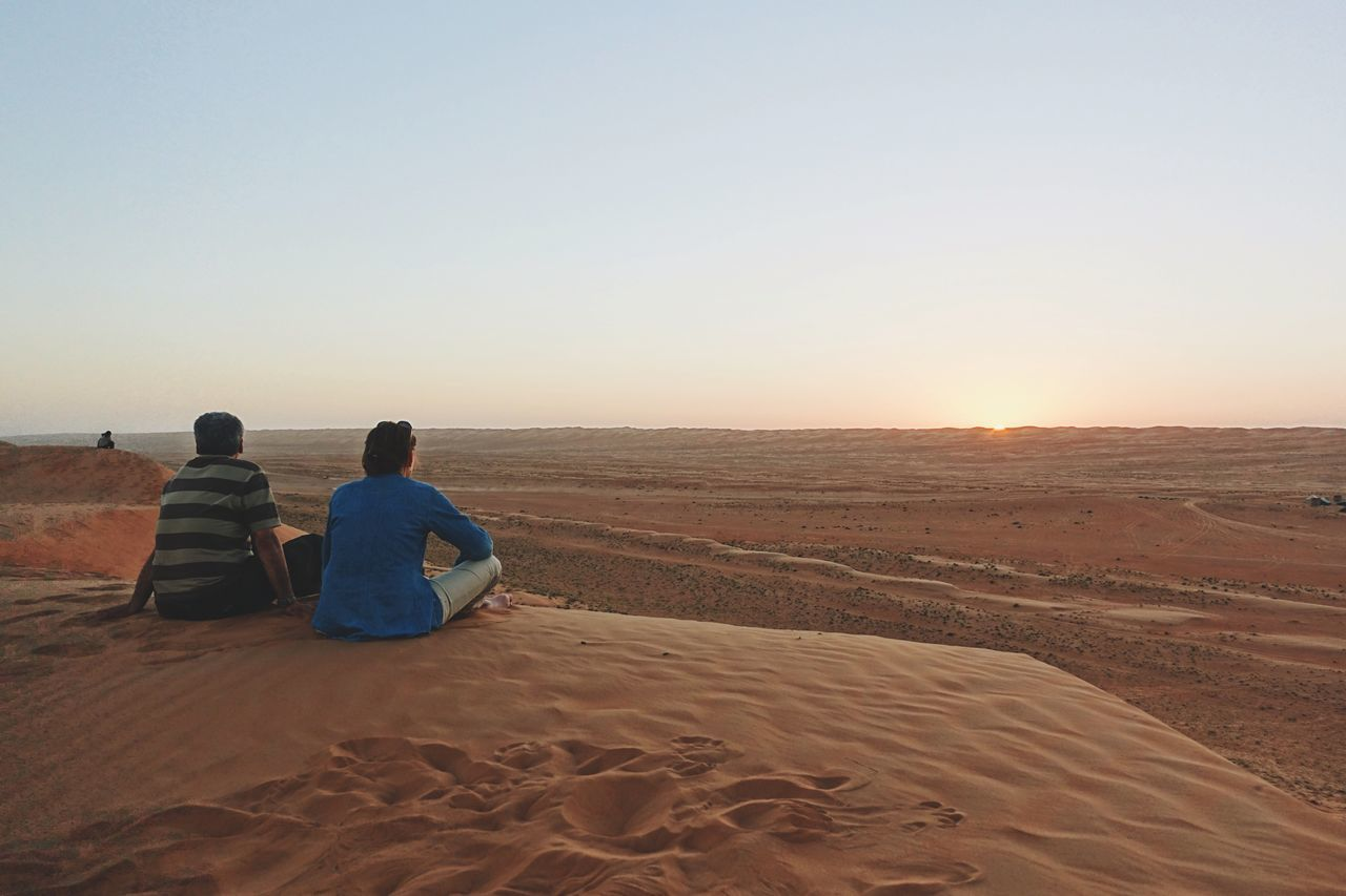 Rear View Oman Clear Sky Sitting Lifestyles Sand Desert Idyllic Women Men Scenics Arid Climate Beauty In Nature Sunset Nature Outdoors Leisure Activity Sky From My Point Of View Watching The Sunset Couple Romantic Naturelovers Travel Vacations