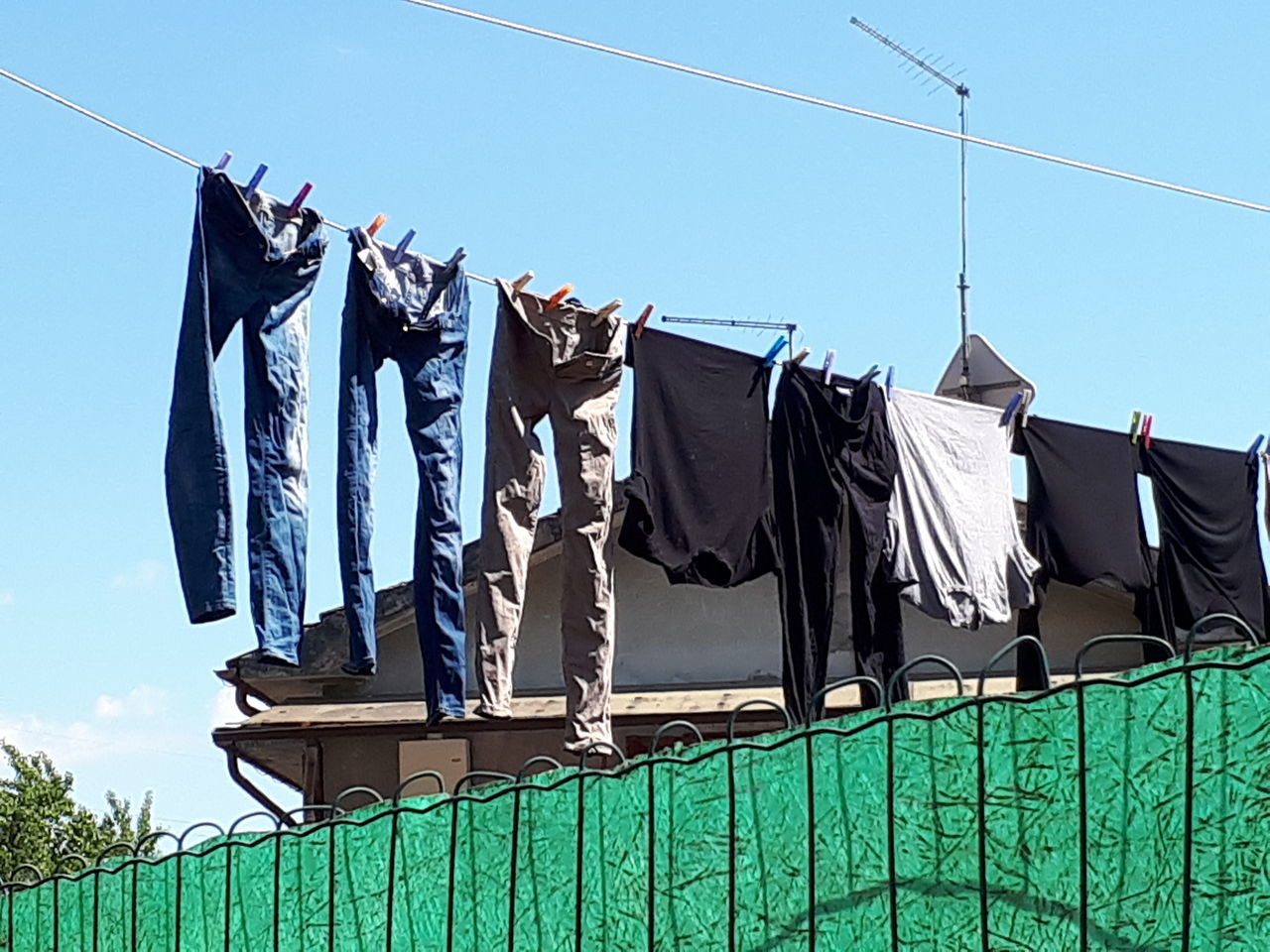 hanging, clothing, low angle view, drying, clothesline, no people, day, outdoors, sky, architecture, clear sky, building exterior