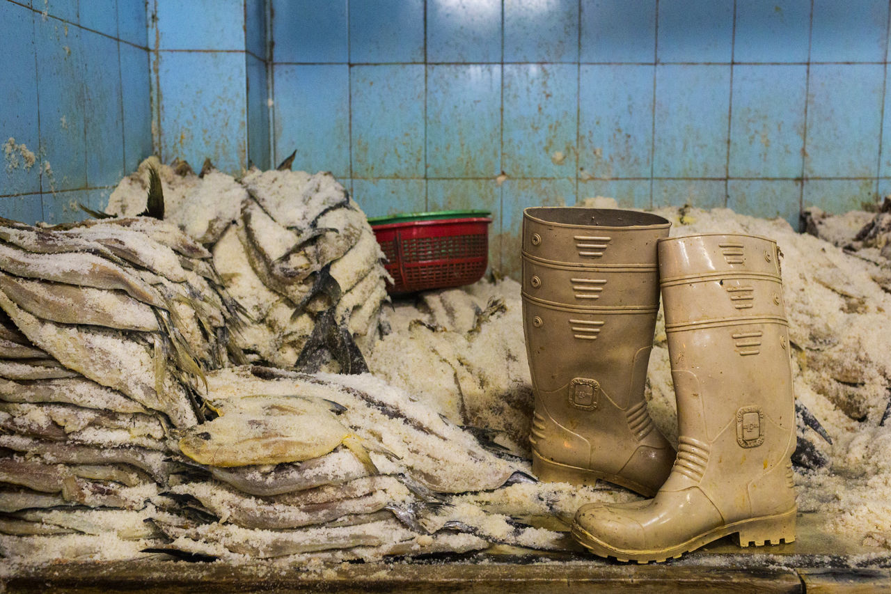 A pair of waterproof boots discarded by fish being cured in Mumbai's fish market Blue Tiles Fresh Fish Mumbai Fish Market Salt Fish Waterproof Boots Work Boots Blue Tiles Boots Fish Fish Market Fresh Fish India Market Mumbai No People Preserved Fishes Rubber Soles Wellies  Wellington Boots