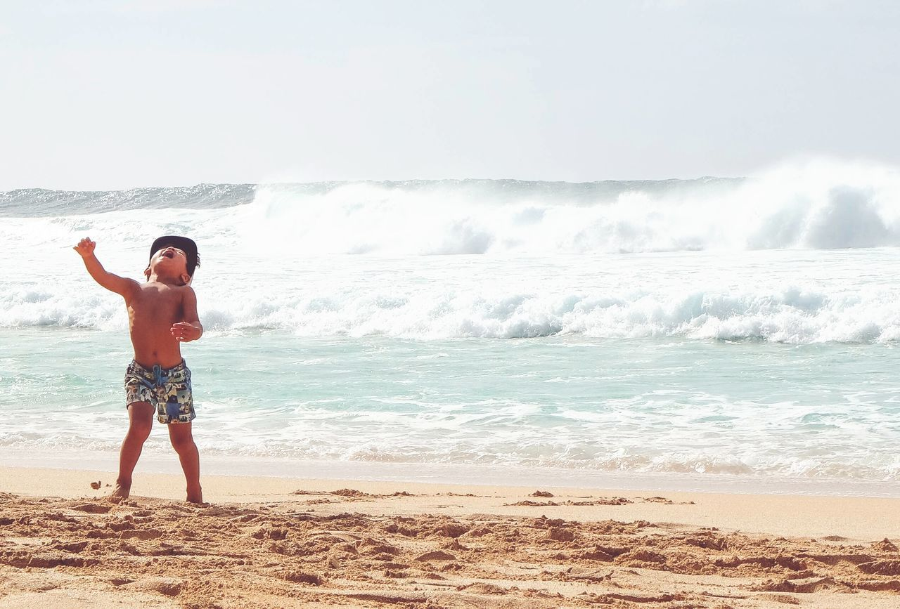 Surf's Up North Shore Hawaii a child screams for joy as waves pound Hawaii's North Shore during the billabong pipe master surf competition.