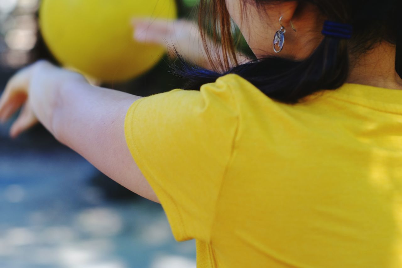 Rear view of woman wearing yellow short and throwing a yellow ball Yellow One Person Only Women One Woman Only People Adult Adults Only Rear View One Young Woman Only Young AdultHuman Hand Human Body Part Lifestyles Day Young Women Close-up Outdoors Playing Ball Asian Girl 30-40 Years Neon Life