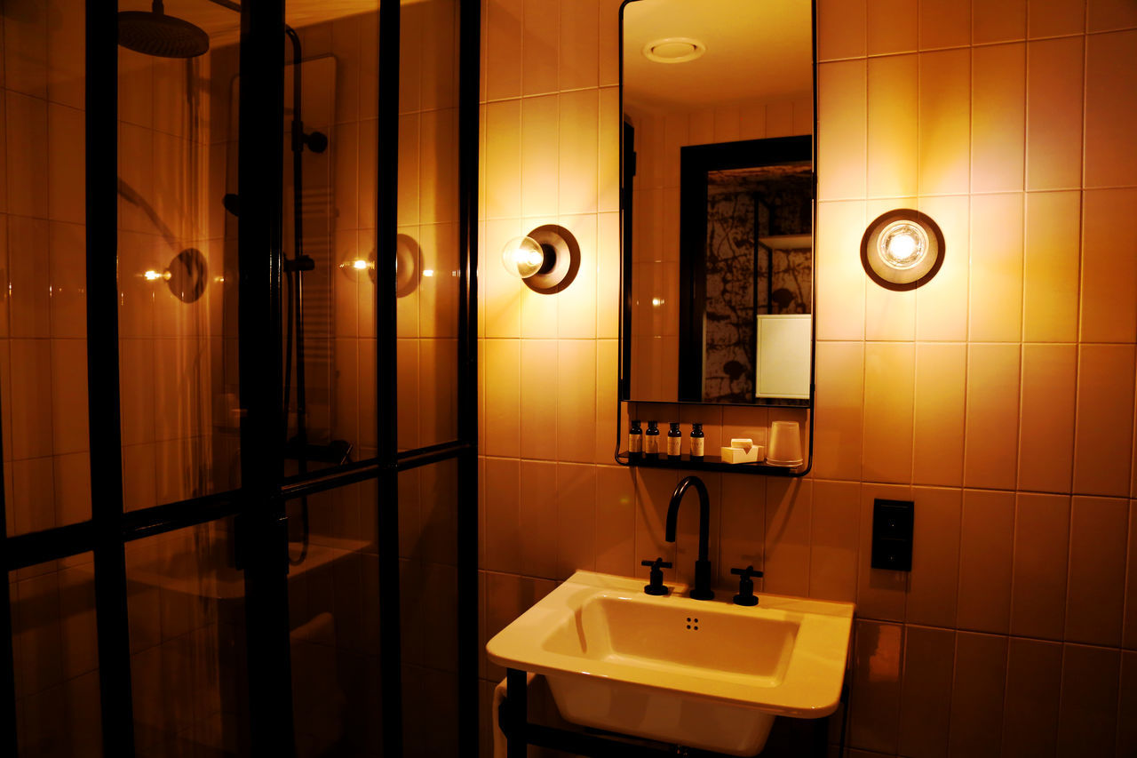 illuminated, indoors, bathroom, hygiene, domestic bathroom, no people, yellow, urinal, architecture, bathroom sink, day