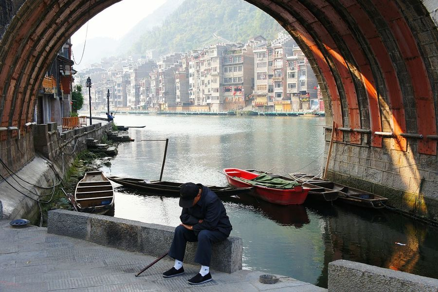 Under the bridge in Zhenyuan, China. Old man takes a rest. The Street Photographer - 2016 EyeEm AwardsTraveling In China China Chinese Culture Wanderlust Travel Photography Guizhou Guizhou,china Zhenyuan Chinese Architecture Under The Bridge Bridge Bridge - Man Made Structure Tired Tiredface Sad Mood Sadness Old Age Traditional Boat Fishing Fishing Boat Walking Cane River Traditional Architecture Showcase April
