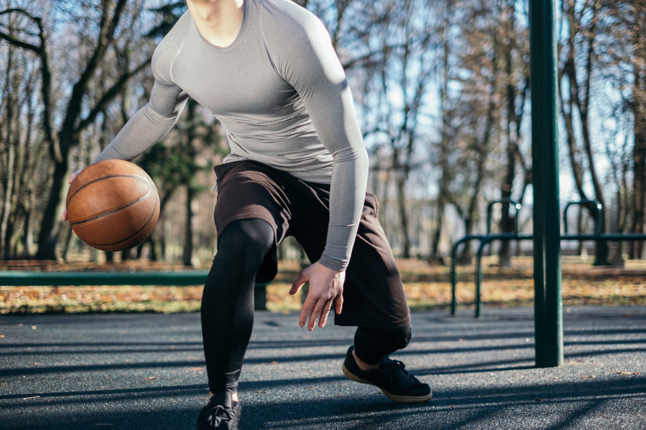 the man plays basketball Activity Adults Only Basketball - Sport City City Life Exercising Healthy Lifestyle Holding Human Body Part Lifestyles Motion One Man Only One Person One Young Man Only Only Men Outdoors People Sport Sports Clothing Vitality Young Adult
