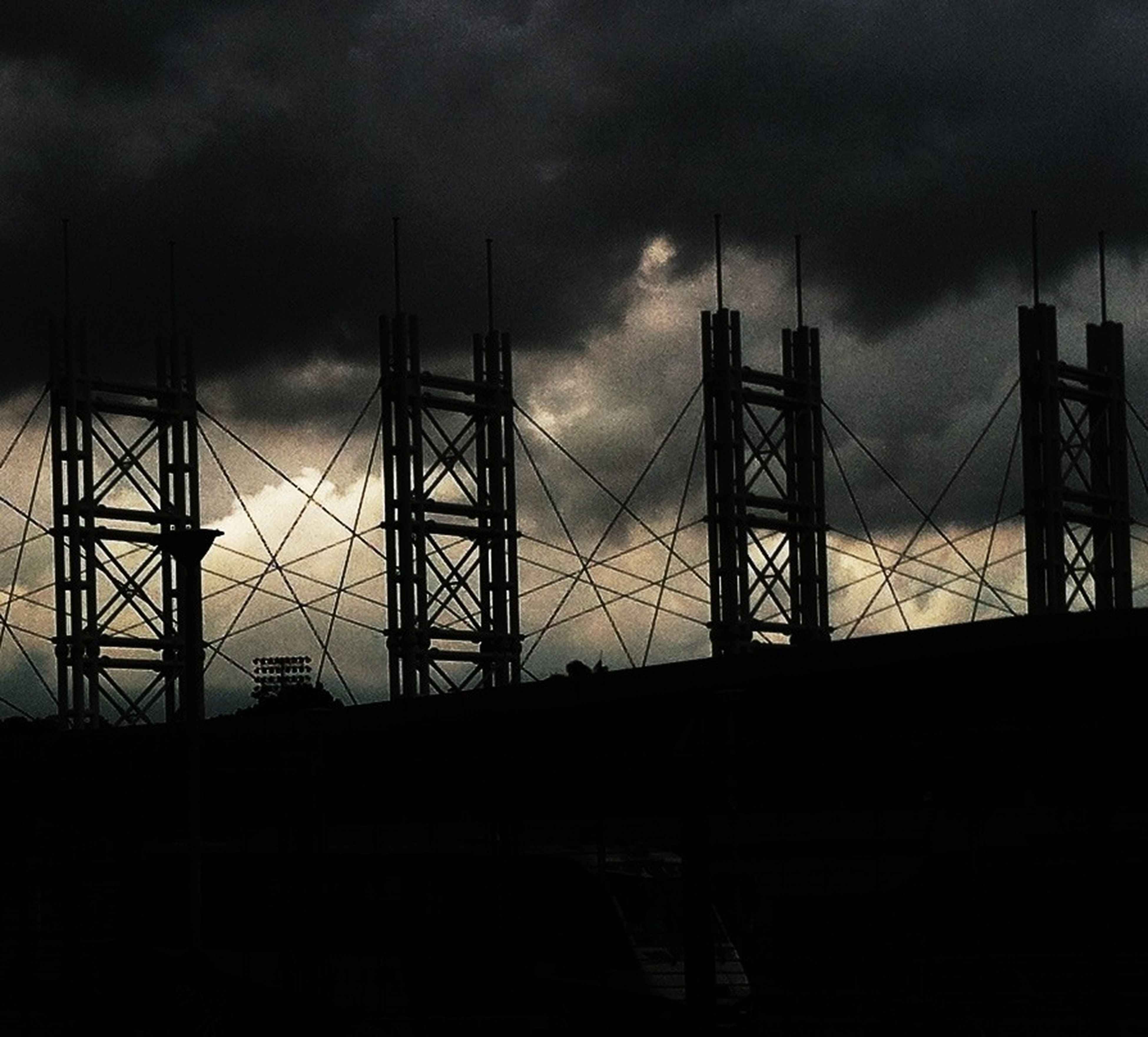 sky, cloud - sky, silhouette, cloudy, built structure, architecture, low angle view, dusk, connection, transportation, cloud, weather, sunset, overcast, outdoors, no people, metal, dark, building exterior, electricity pylon