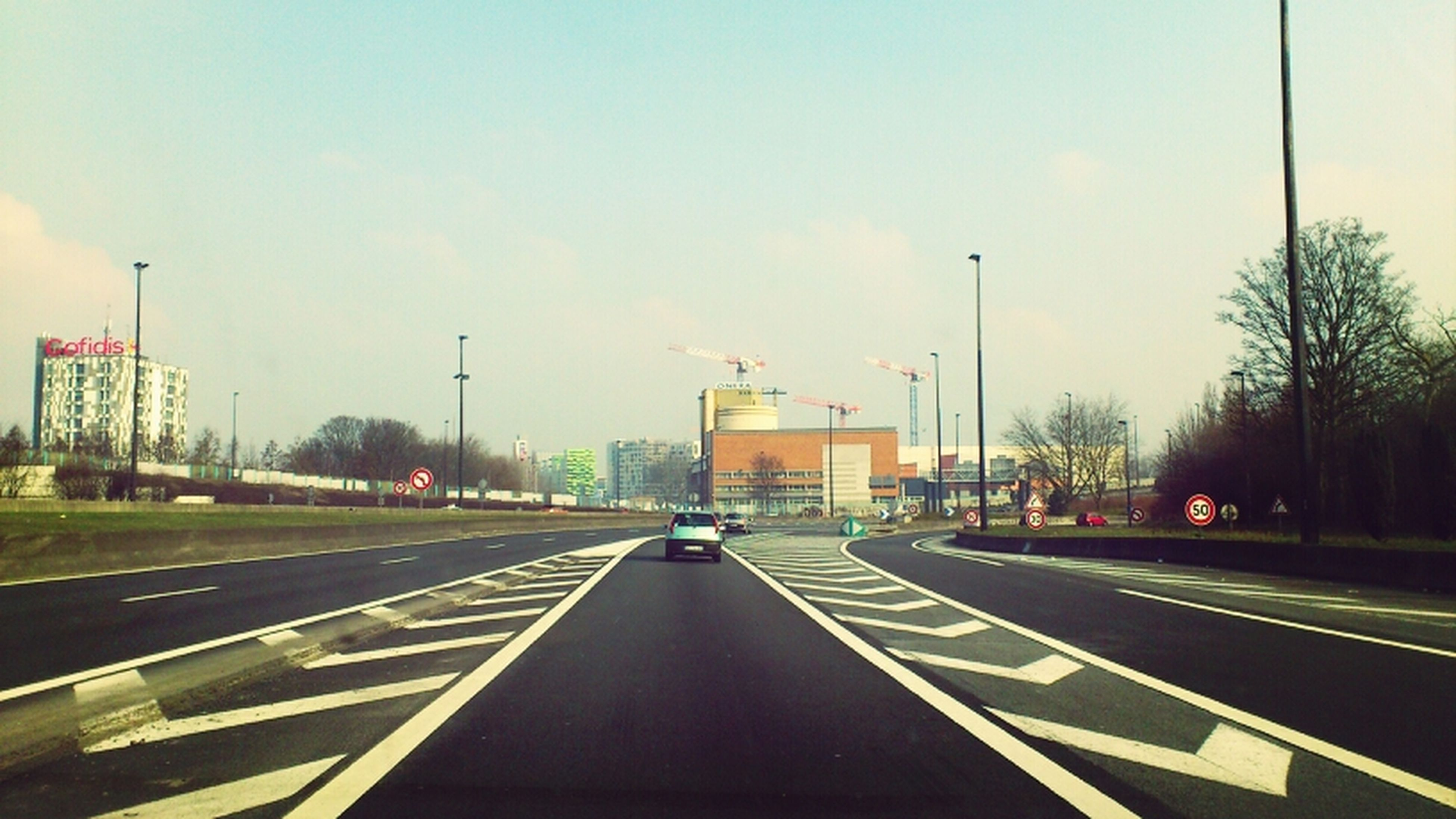 transportation, road, road marking, the way forward, car, sky, mode of transport, street light, diminishing perspective, land vehicle, street, vanishing point, on the move, cloud - sky, built structure, empty, tree, highway, travel, building exterior