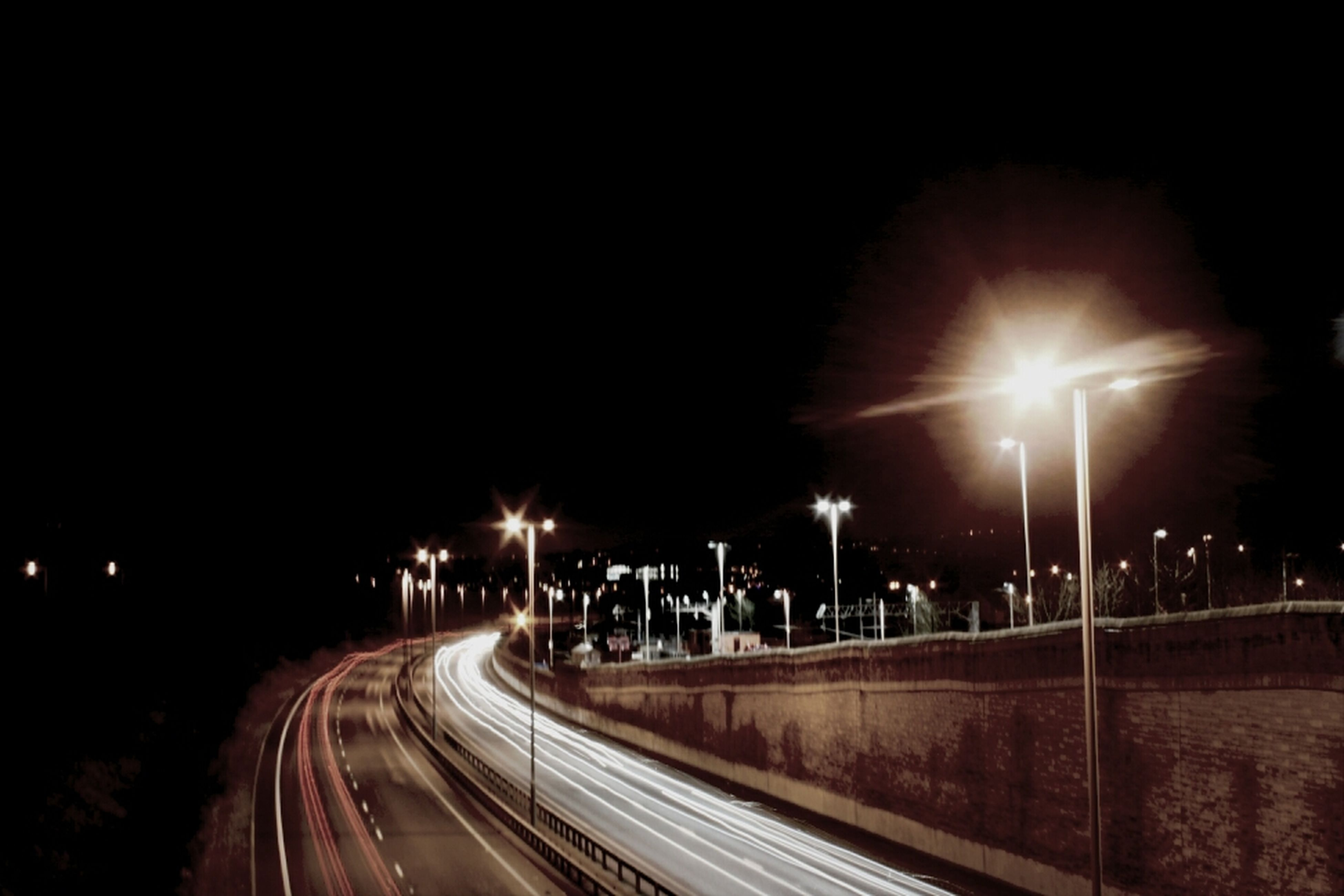 night, illuminated, long exposure, light trail, street light, transportation, road, speed, motion, lighting equipment, street, the way forward, blurred motion, light - natural phenomenon, copy space, city, glowing, clear sky, diminishing perspective, outdoors