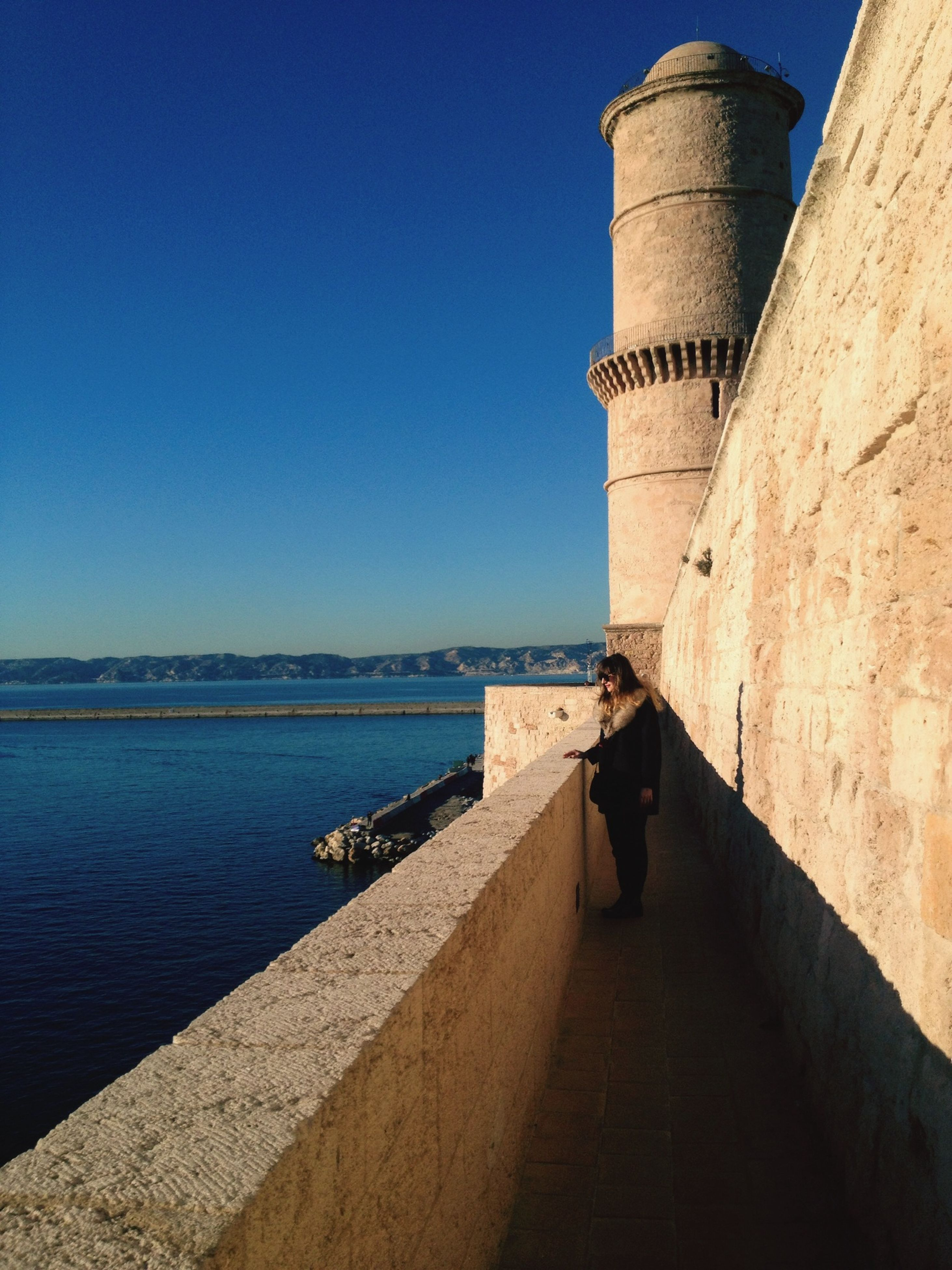 clear sky, architecture, built structure, blue, building exterior, copy space, sea, water, the way forward, sunlight, lifestyles, leisure activity, tourism, day, horizon over water, men, rear view, person