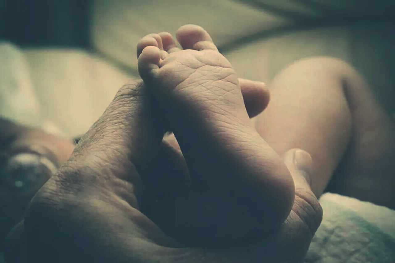 human foot, barefoot, human body part, human leg, low section, sole of foot, baby, close-up, babyhood, togetherness, real people, indoors, human skin, human hand, childhood, newborn, bonding, fragility, men, day, adult, people