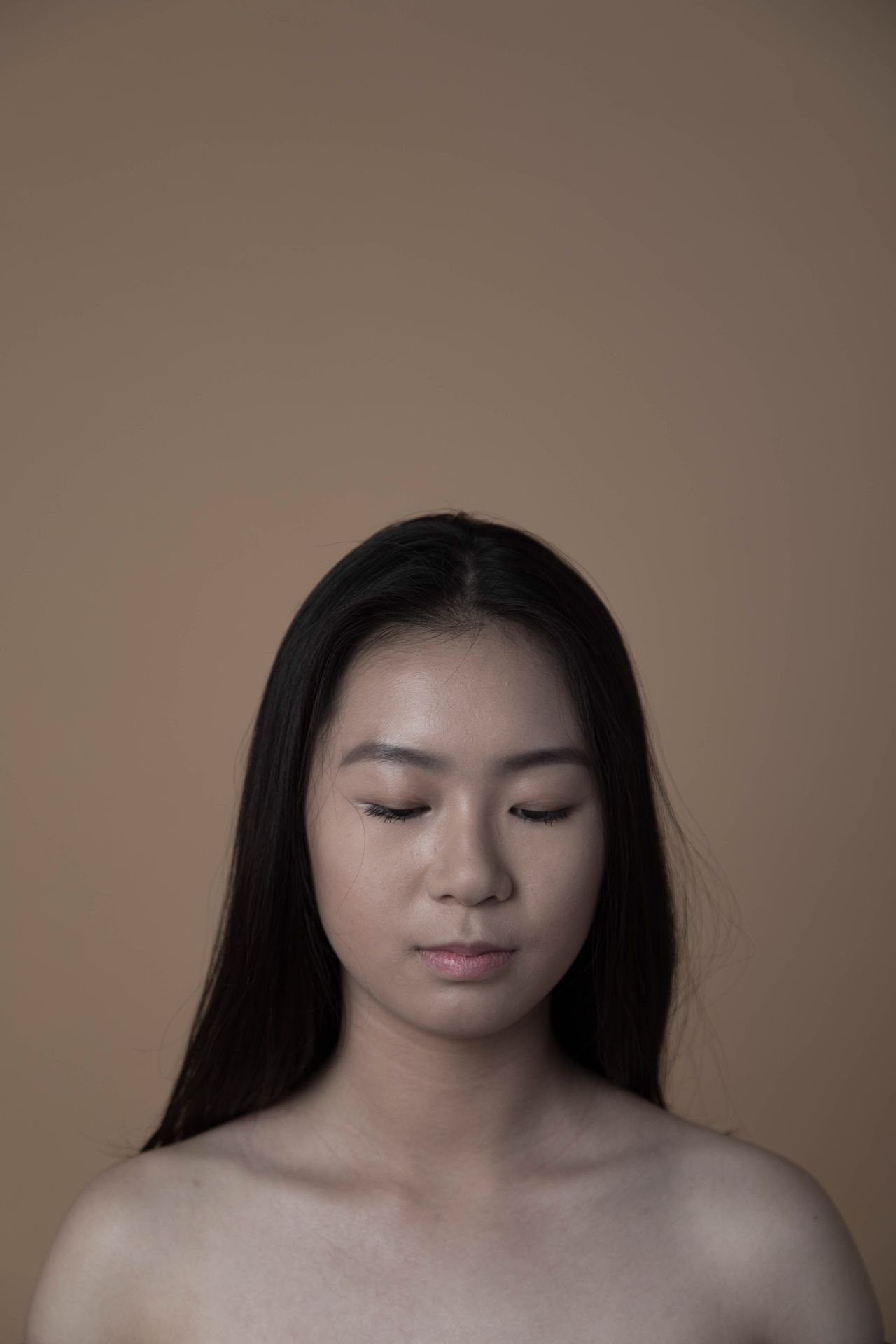 Eyes Closed one person studio shot front view headshot black hair beautiful woman young adult Shirtless real people lifestyles colored background beige background beauty close-up young women indoors day Adult people The Portraitist - 2017 EyeEm Awards EyeEmNewHere