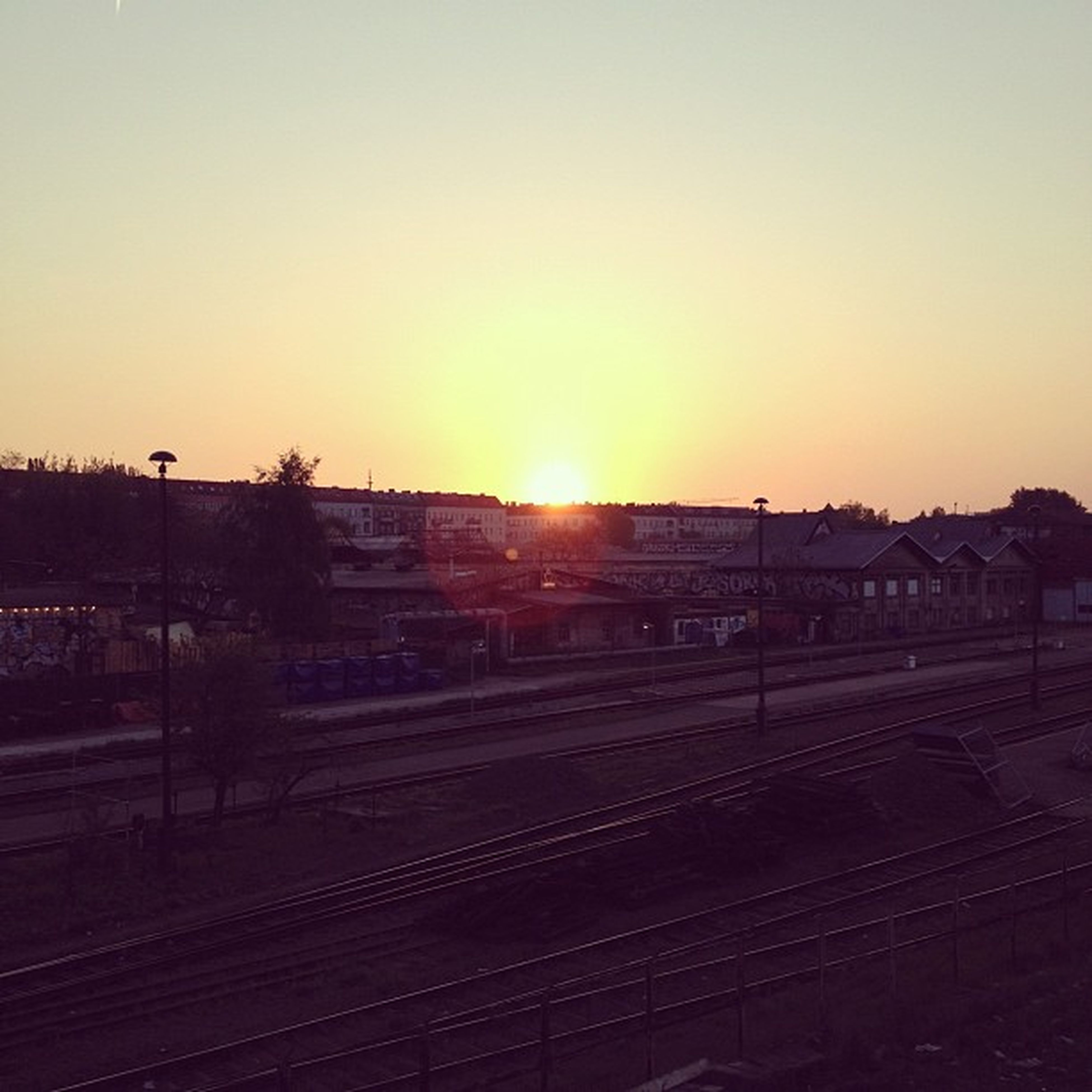 sunset, sun, clear sky, orange color, copy space, transportation, railroad track, sunlight, rail transportation, sky, silhouette, landscape, built structure, sunbeam, lens flare, nature, outdoors, building exterior, no people, road