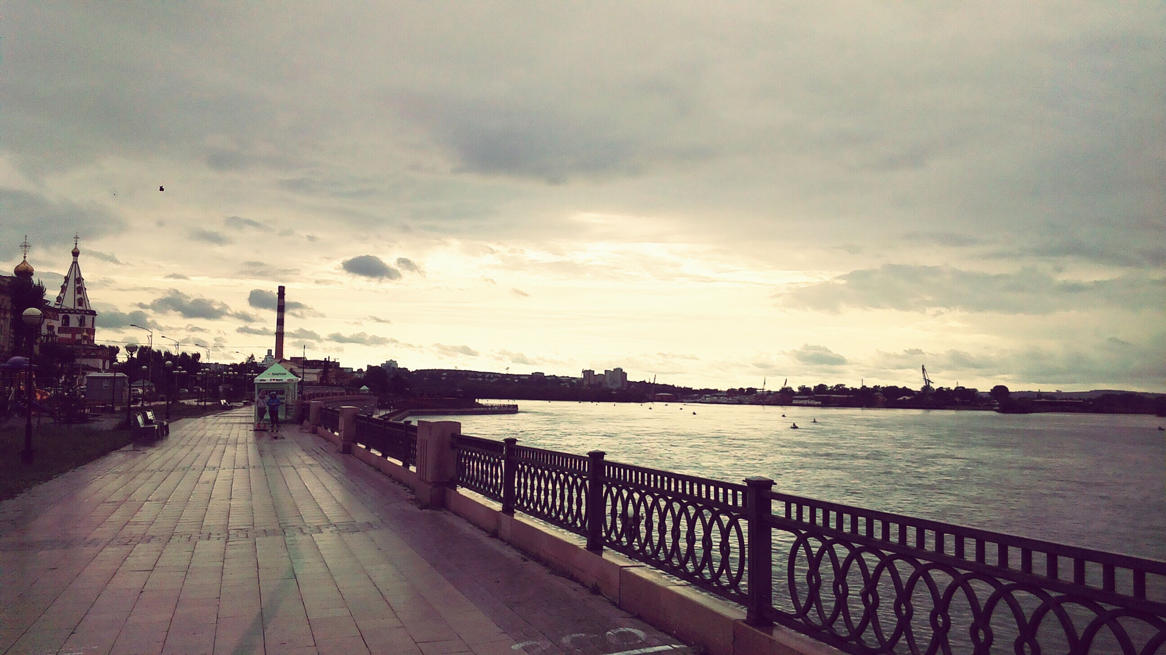 railing, water, street light, cloud, empty, road, sky, city, street, bench, the way forward, river, incidental people, pathway, promenade, lamp post, long, day, calm, diminishing perspective, walkway, cloud - sky, footpath, tranquility, city life, tranquil scene, sea, outdoors, cloudy, park bench