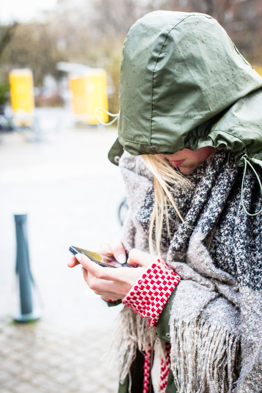 Woman In Raincoat Using Mobile Phone On Street