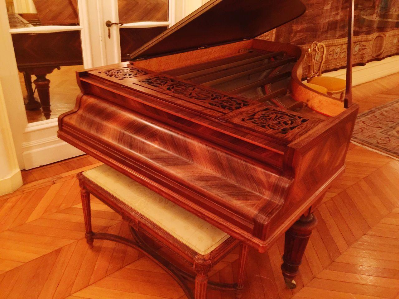Seat By Piano On Hardwood Floor