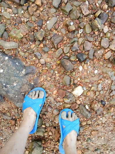 น้ำขึ้นละ บ๊ายบ่ายหอย Low Section Human Leg Shoe One Person Human Foot Day High Angle View Personal Perspective Real People Beach Outdoors Human Body Part Standing Sandal Pair Sand Blue Nature Close-up One Man Only
