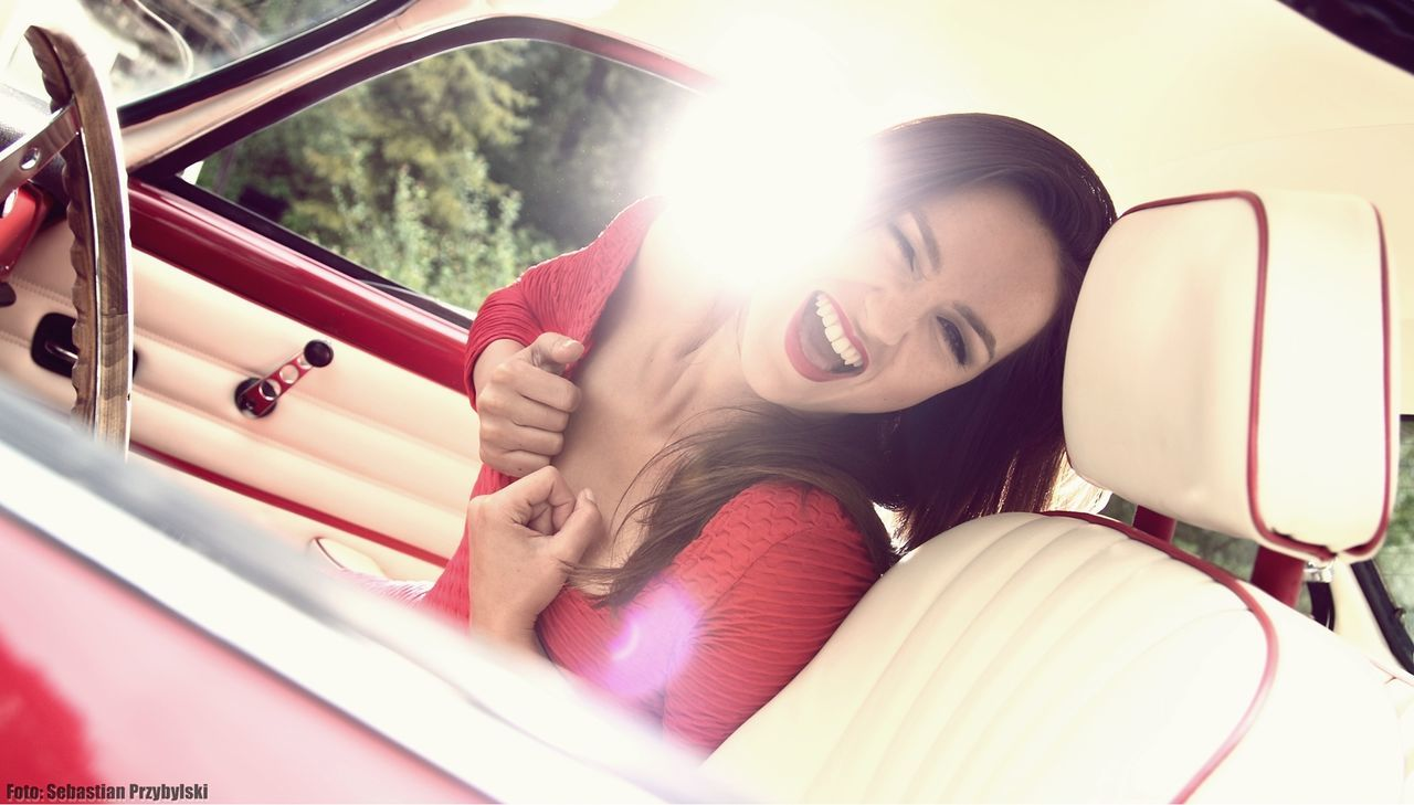 car, transportation, young adult, smiling, young women, mode of transport, happiness, day, one person, land vehicle, car interior, sitting, cheerful, real people, beautiful woman, outdoors, one young woman only, adult, people