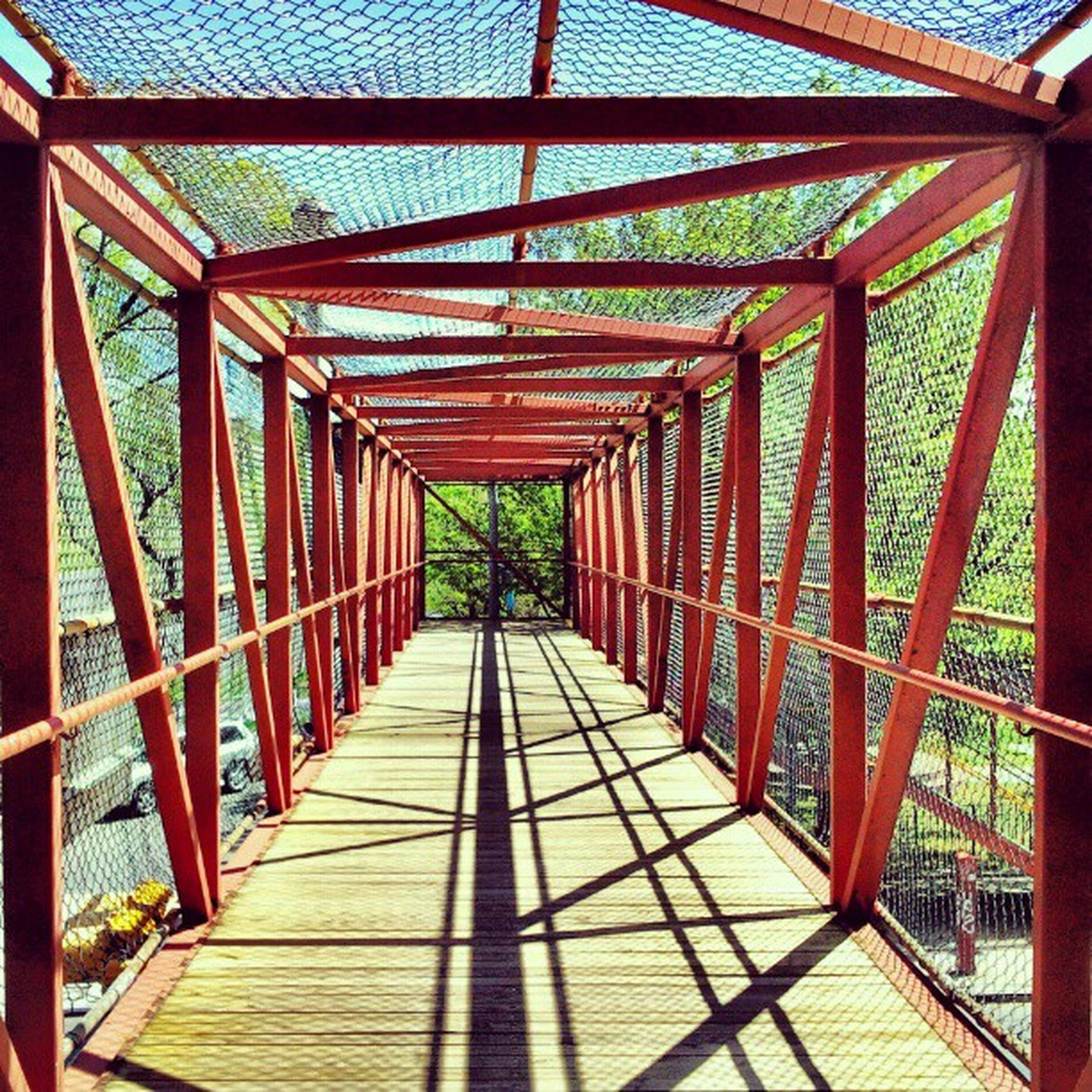 built structure, architecture, the way forward, railing, diminishing perspective, footbridge, bridge - man made structure, connection, vanishing point, metal, pattern, wood - material, day, sunlight, walkway, no people, indoors, engineering, shadow