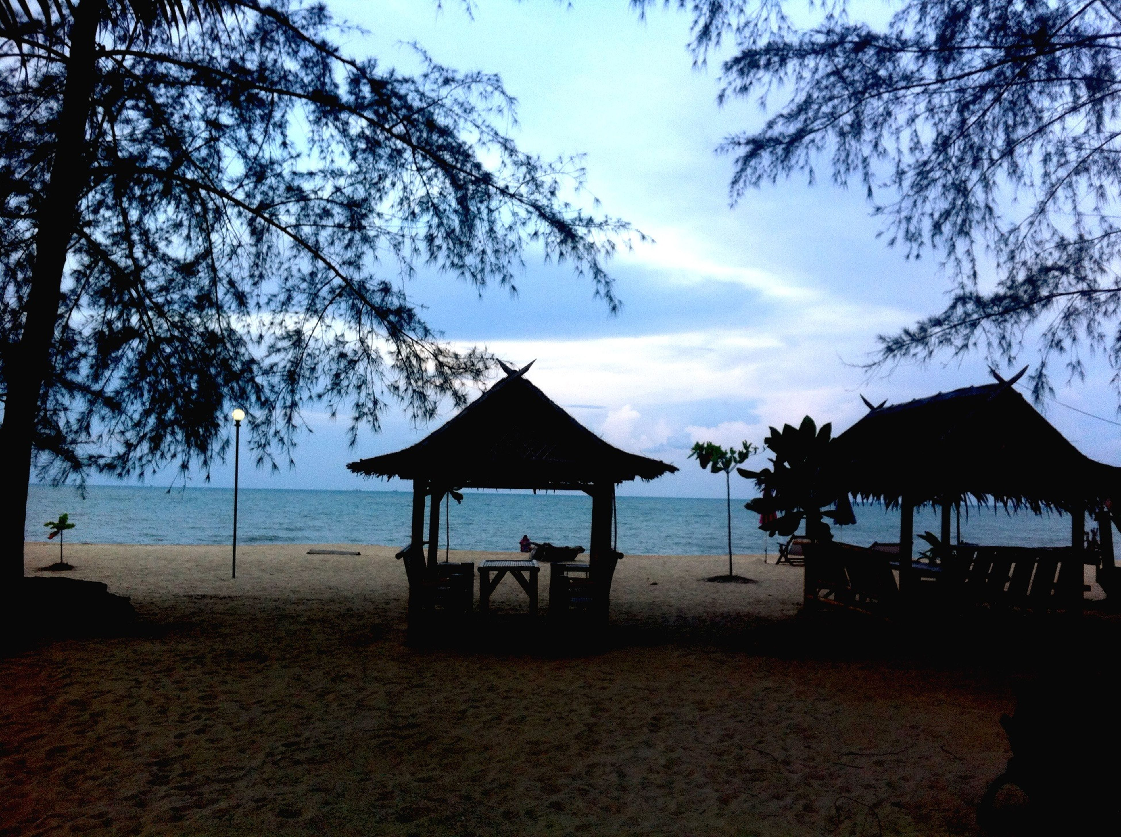 beach, sea, water, sand, tranquil scene, tranquility, tree, shore, horizon over water, sky, scenics, beauty in nature, nature, vacations, idyllic, relaxation, absence, thatched roof, incidental people, tourism
