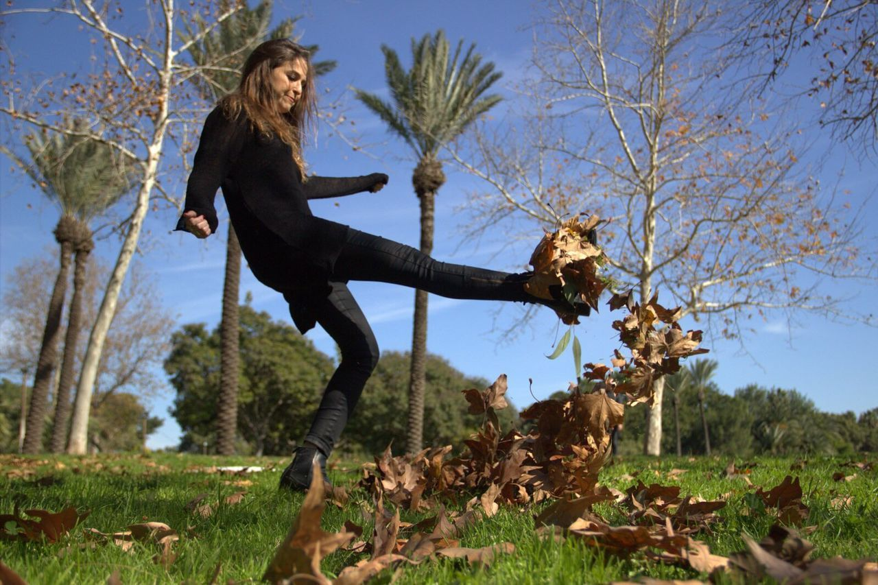 Full Length Of Woman Kicking Dry Leaves