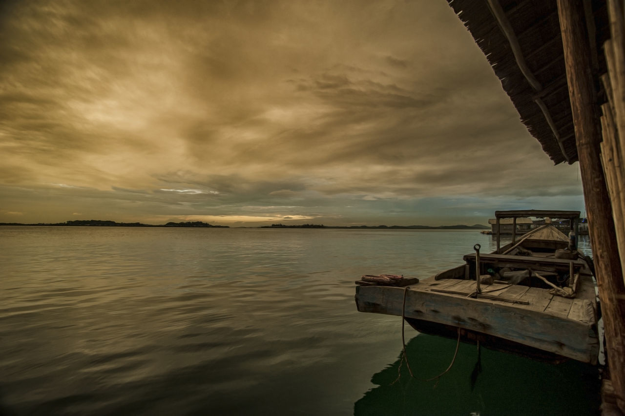 Boat Moored By Pier In Sea Against Cloudy Sky During Sunset