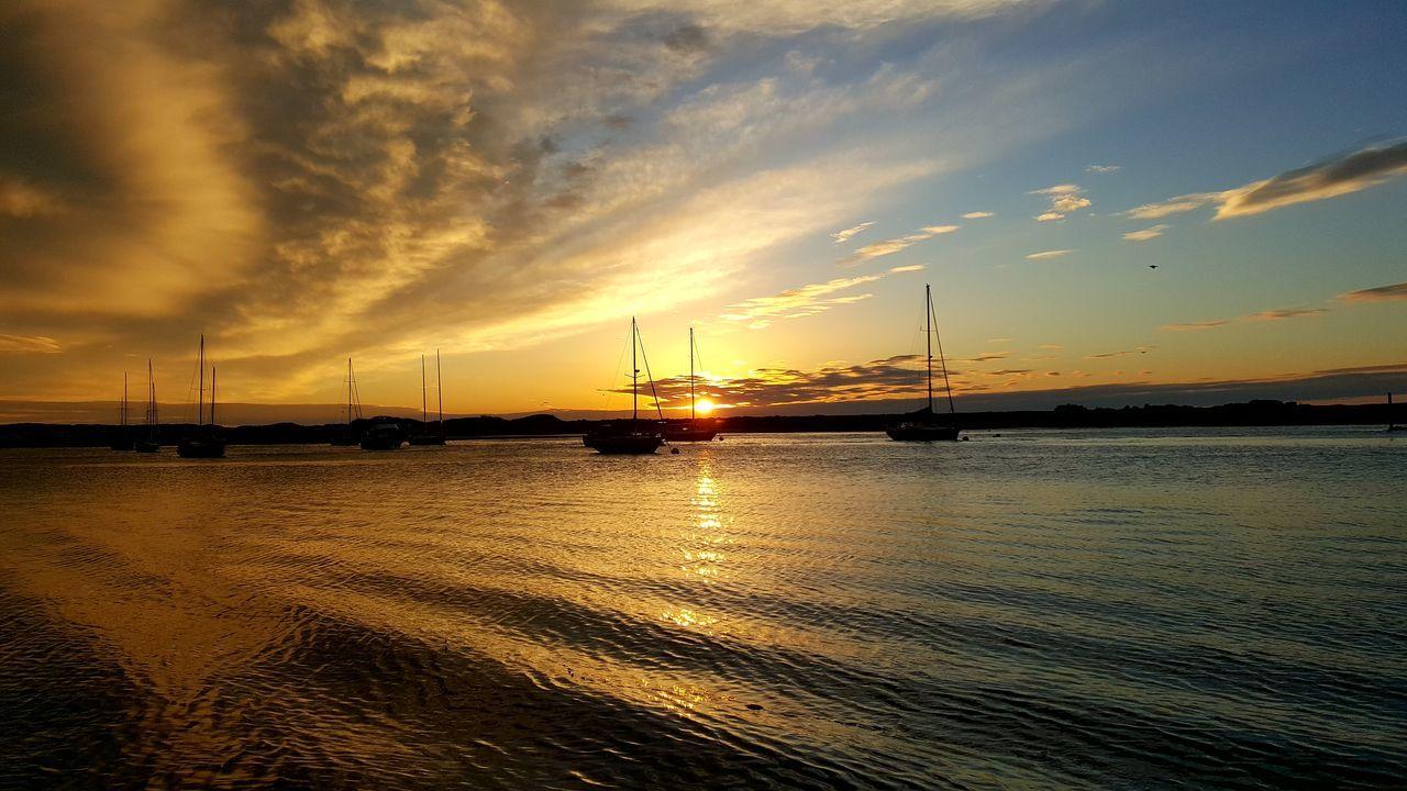 Water Sunset Sea Sky Dramatic Sky Beach Outdoors Cloud - Sky Nautical Vessel No People Sea And Sky Harbor Dramatic Sky Reflection Boats Orange Sky Orange Color Landscape