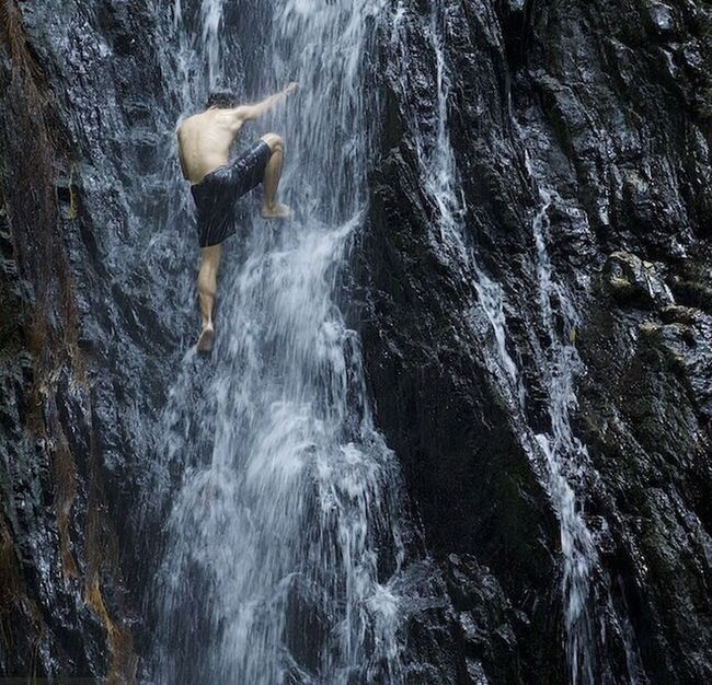 Orangutan researcher and photo team member Robert Rodriguez Suro (@rrsuro) cools off with a little waterfall climbing during a lull on the orang urban action in the Ulu Ai forest, Sarawak, Malasyan Borneo. Photo by @TimLaman on assignment for @NatGeo. Malasyan Borneo SavePGorangutans
