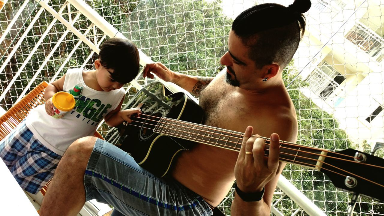 playing, two people, real people, guitar, leisure activity, music, togetherness, casual clothing, musical instrument, lifestyles, indoors, sitting, bonding, musician, performance, young adult, plucking an instrument, day, fretboard