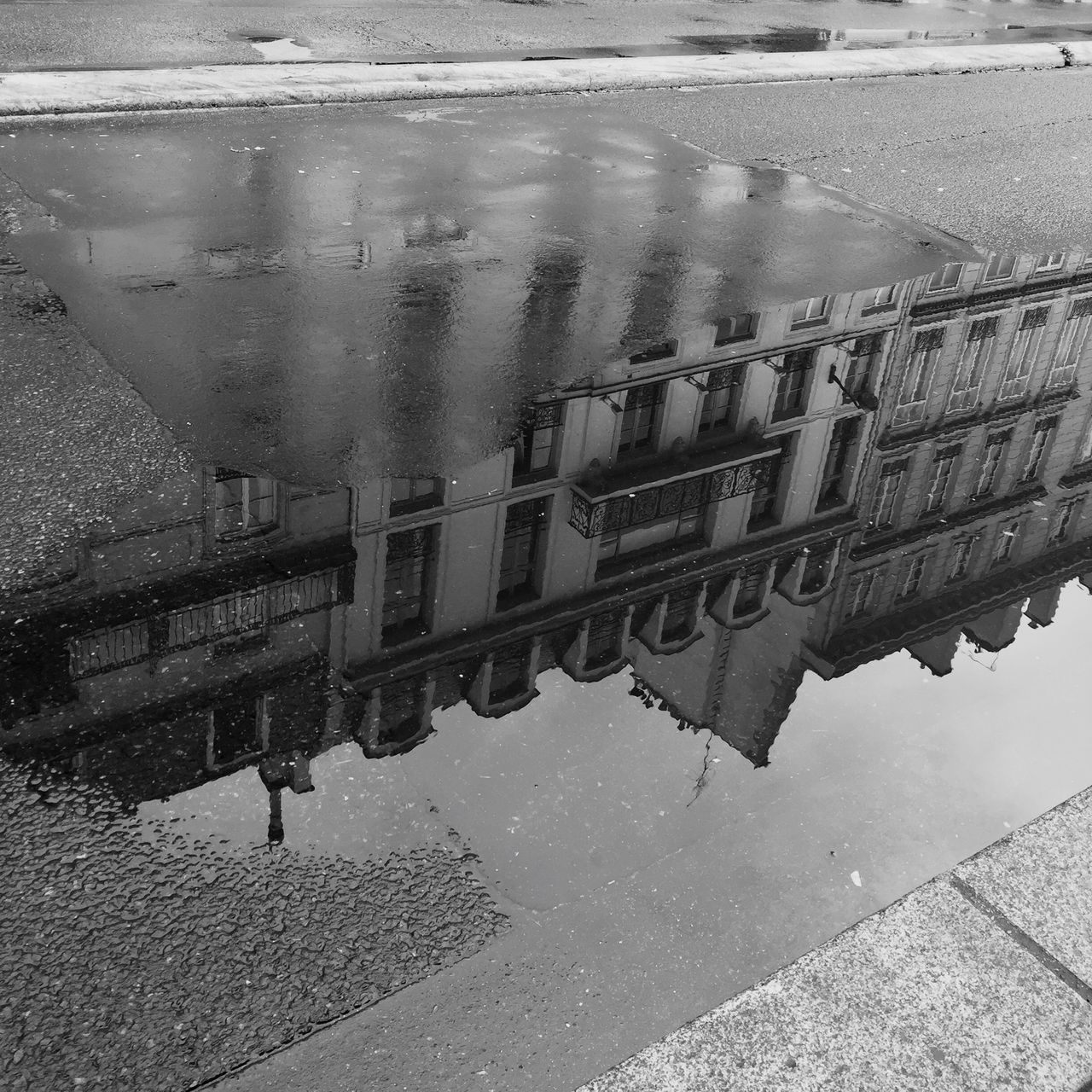 High Angle View Of Building Reflection On Street Puddle