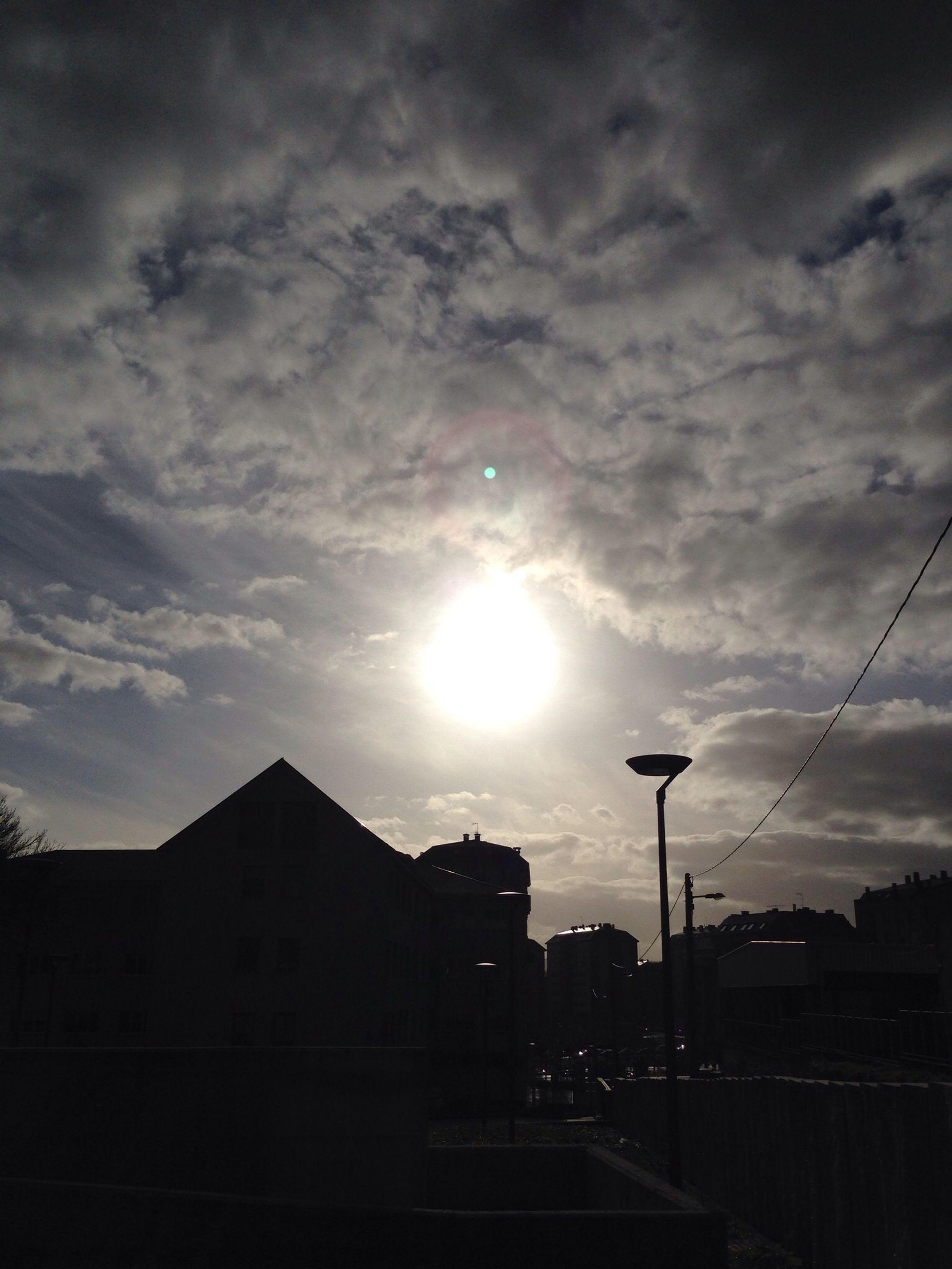 sky, building exterior, built structure, sun, architecture, cloud - sky, street light, silhouette, sunset, sunbeam, sunlight, cloudy, city, cloud, lens flare, low angle view, building, outdoors, street, no people