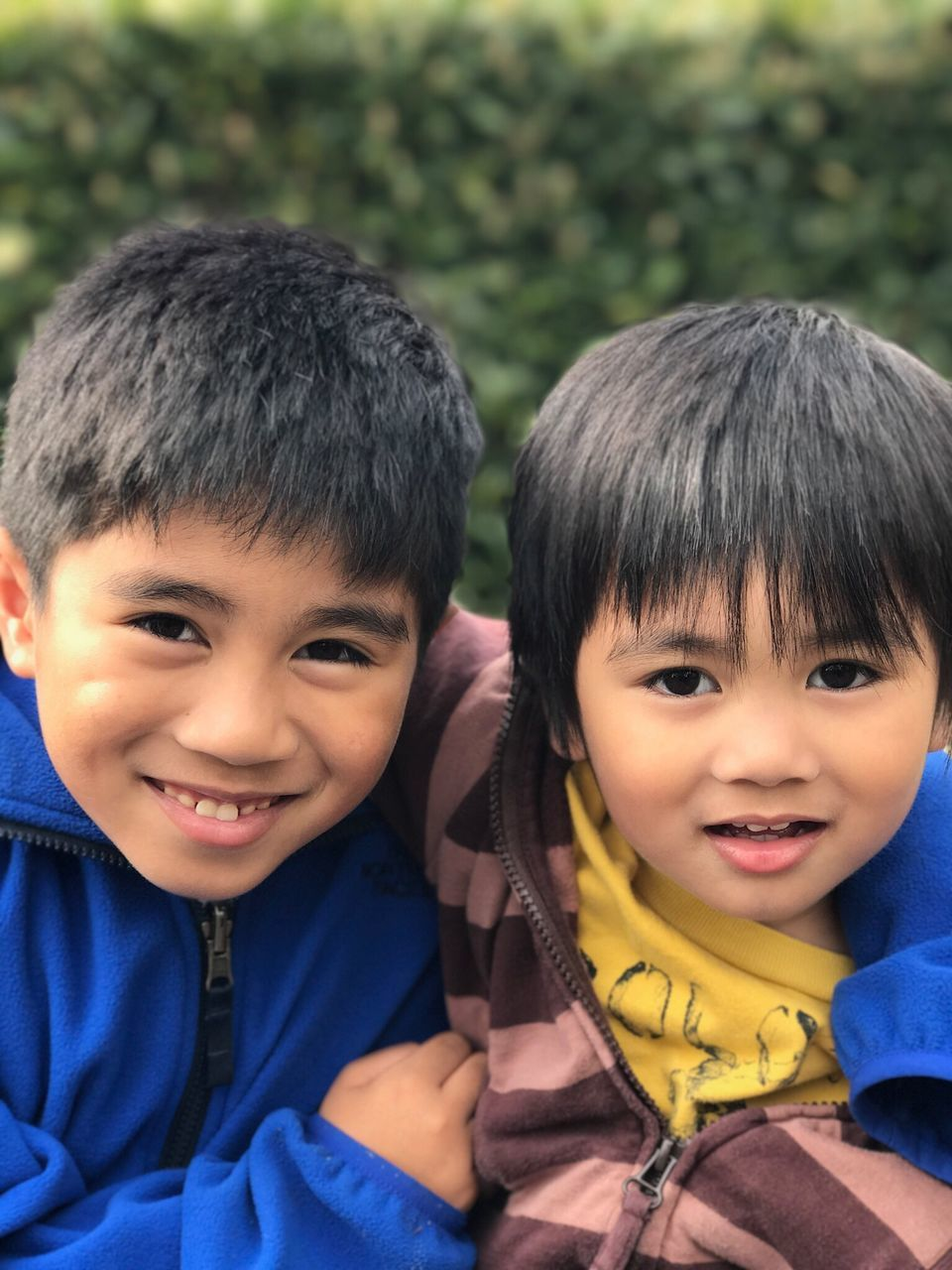 two people, looking at camera, childhood, smiling, real people, boys, portrait, innocence, sibling, happiness, black hair, togetherness, bonding, cute, outdoors, day, cheerful, friendship, close-up