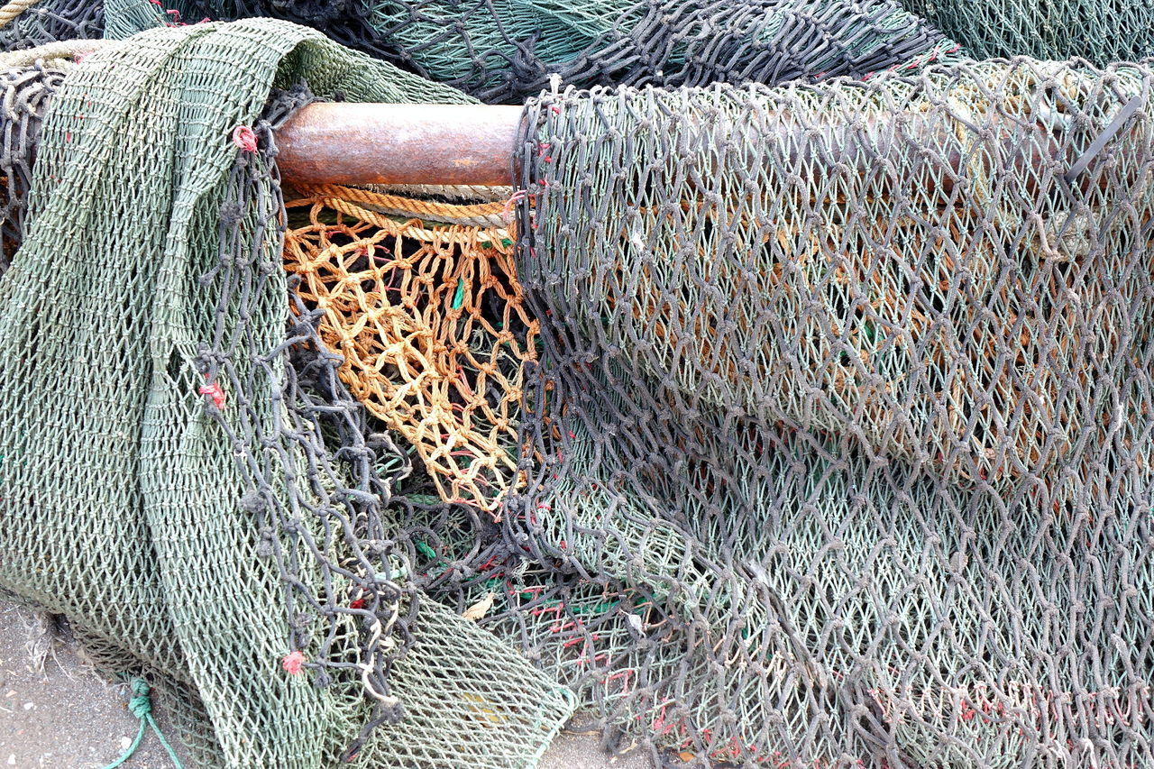 A bunch of old broken fishing nets are lying on the docks Abandoned Broken Fabric Fishing Net Fishing Tackle Mesh Nets Netting Pattern Still Life Woven