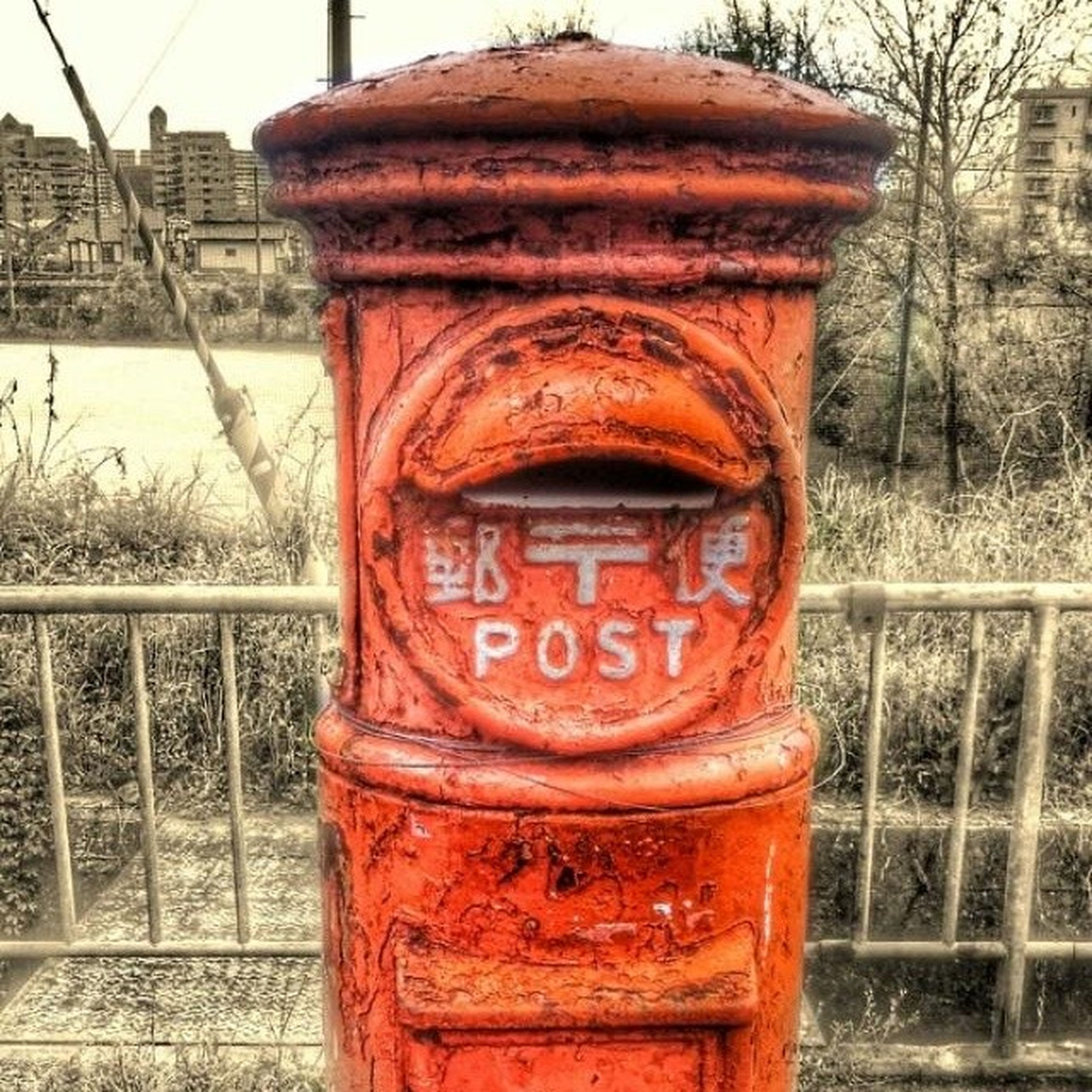 building exterior, architecture, built structure, metal, close-up, red, old, tree, day, rusty, text, outdoors, weathered, no people, focus on foreground, water, western script, metallic, safety, protection