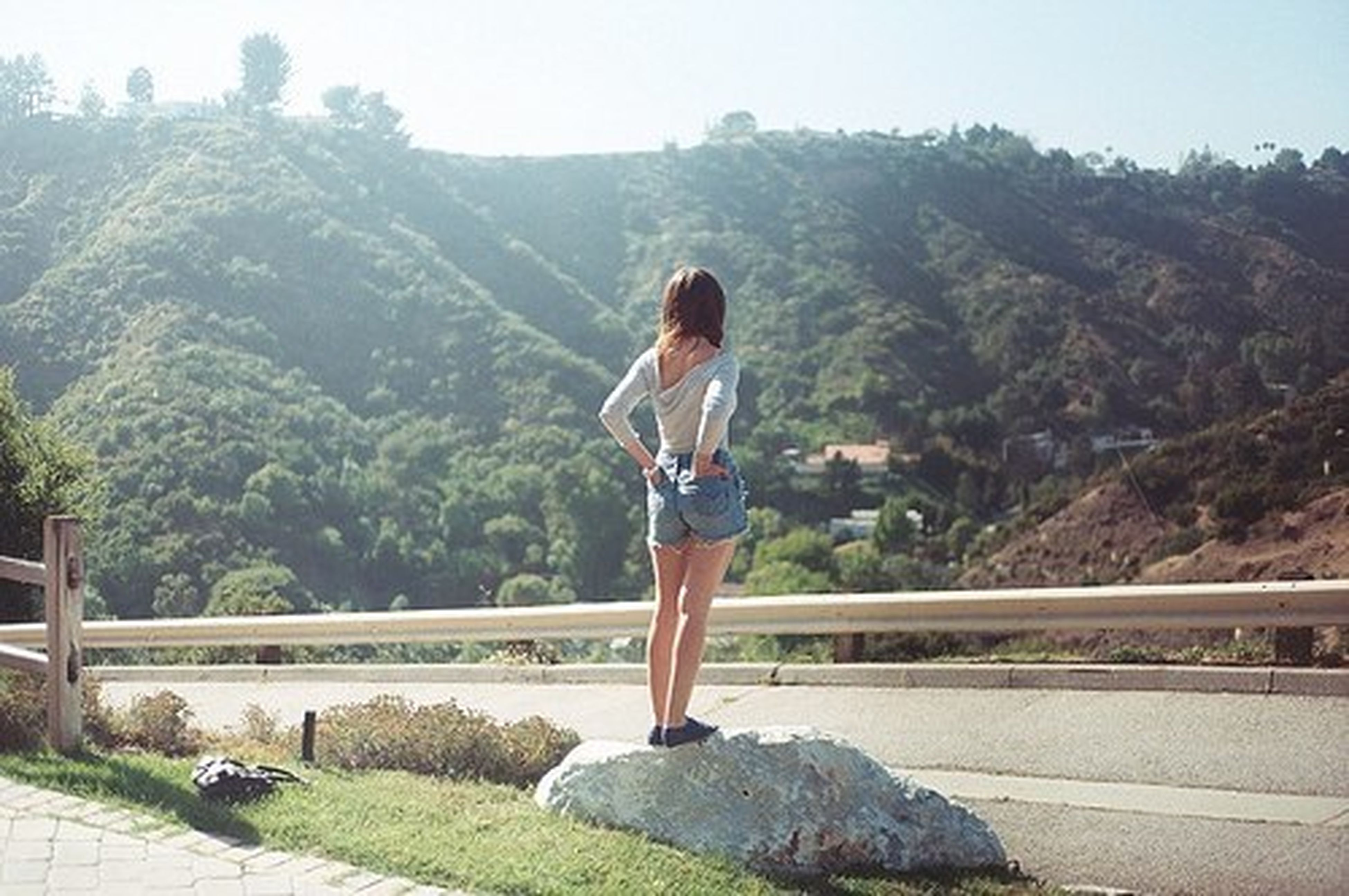 lifestyles, full length, casual clothing, mountain, young adult, leisure activity, railing, standing, person, tree, young women, mountain range, bridge - man made structure, looking at camera, nature, rock - object, day