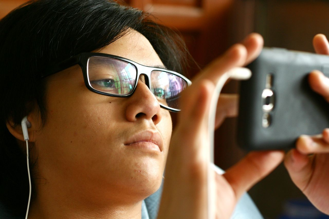 real people, close-up, indoors, women, one person, eyeglasses, technology, day, human hand