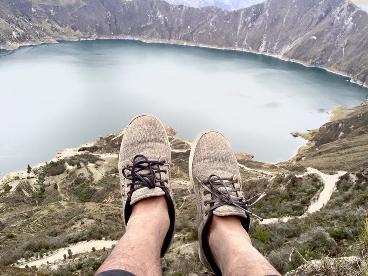 mountain, shoe, low section, human leg, one person, rock - object, personal perspective, hiking, nature, adventure, day, scenics, outdoors, cliff, real people, mountain peak, human body part, lake, mountain range, men, leisure activity, lifestyles, water, landscape, beauty in nature, standing, one man only, climbing, sky, people, only men, adult, adults only
