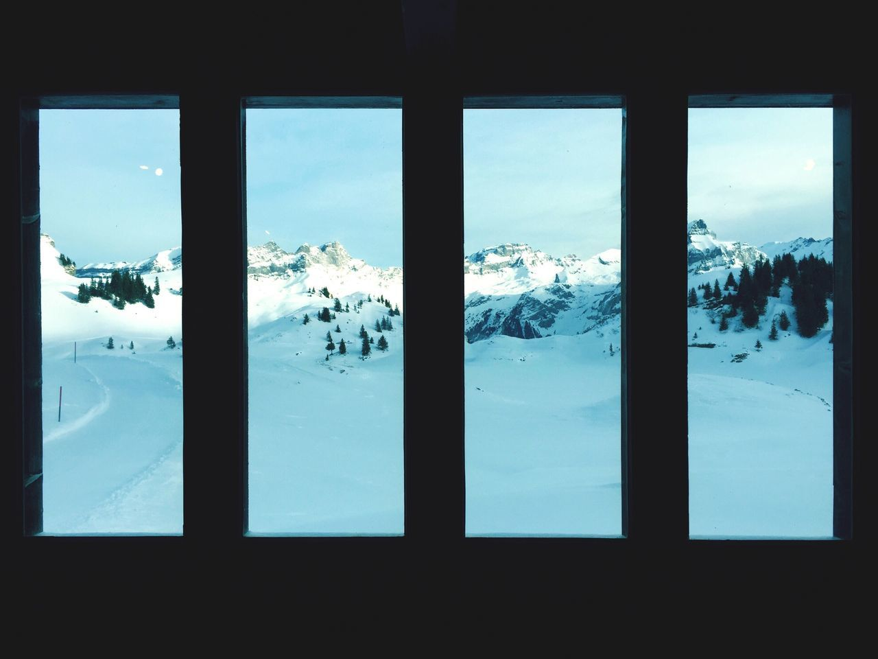 Snow Covered Landscape Against Sky Seen Through Window