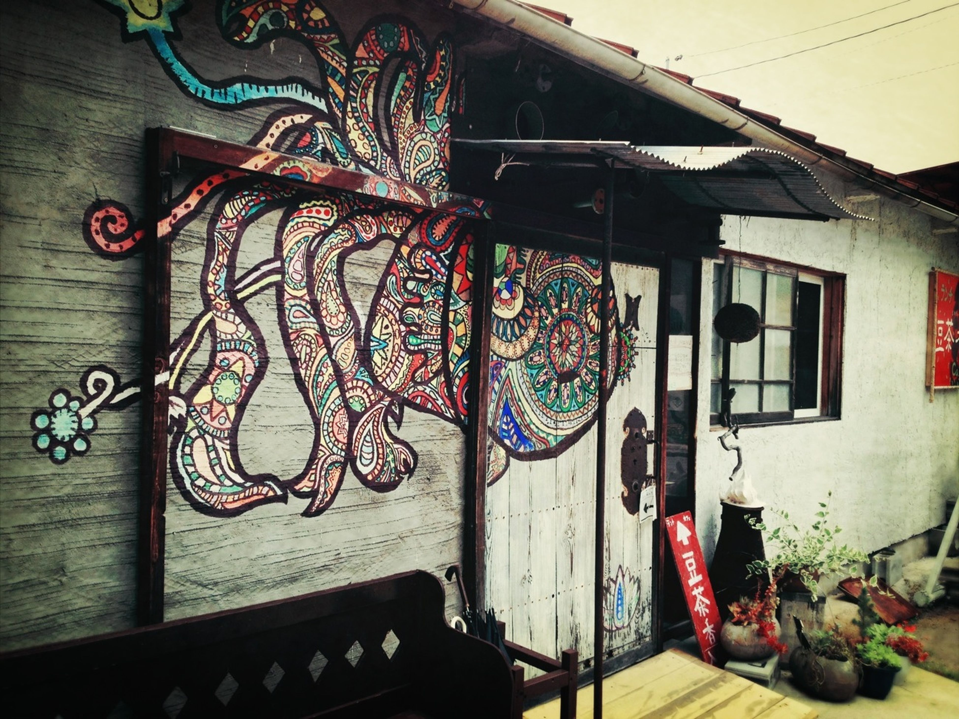 indoors, art and craft, art, creativity, wood - material, wall - building feature, house, built structure, architecture, graffiti, hanging, multi colored, no people, door, decoration, home interior, wall, design, building exterior, day