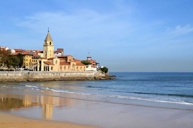 View of San Pedro church at San Lorenzo beach in Gijon, Asturias, Spain Architecture Asturias Beach Blue Cantabrian Sea Church City Cloud - Sky Gijón Horizon Over Water Nature Ocean Outdoors Place Of Worship Religion Scenics Sea Shore Tourism Tranquil Scene Travel Village Water Waterfront Wave