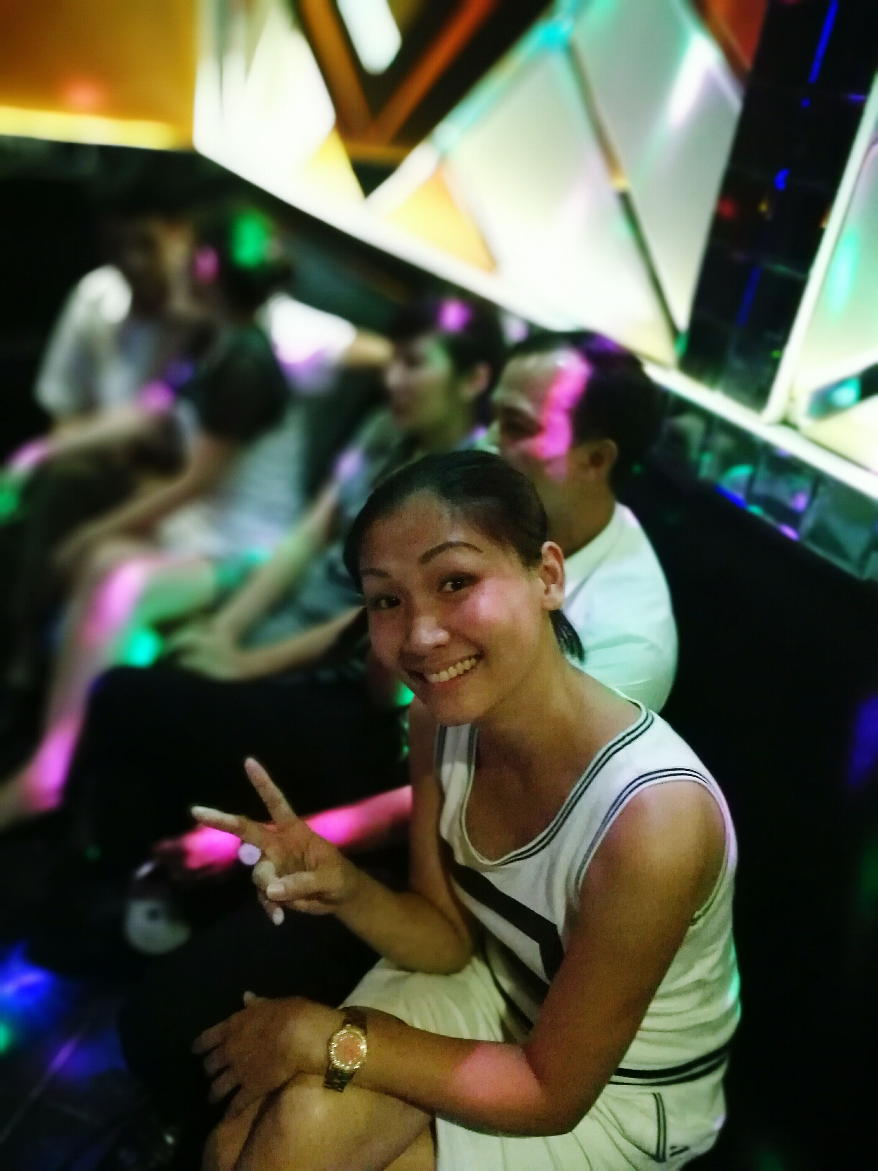 indoors, young adult, young women, leisure activity, front view, person, looking at camera, focus on foreground, casual clothing, multi colored, nightclub