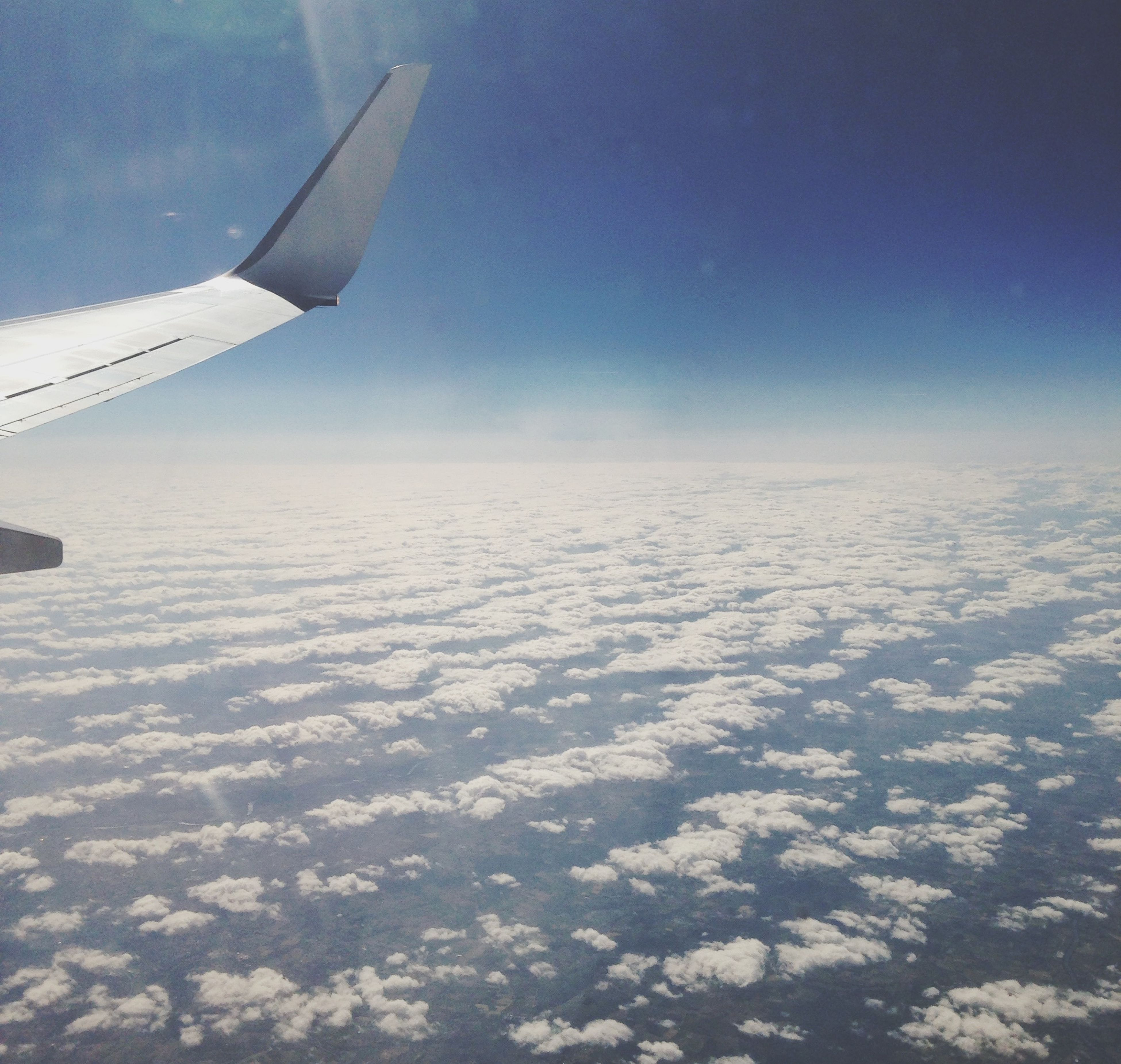 flying, transportation, airplane, air vehicle, aircraft wing, sky, mode of transport, beauty in nature, snow, scenics, nature, landscape, part of, white color, winter, aerial view, tranquil scene, blue, cropped, tranquility