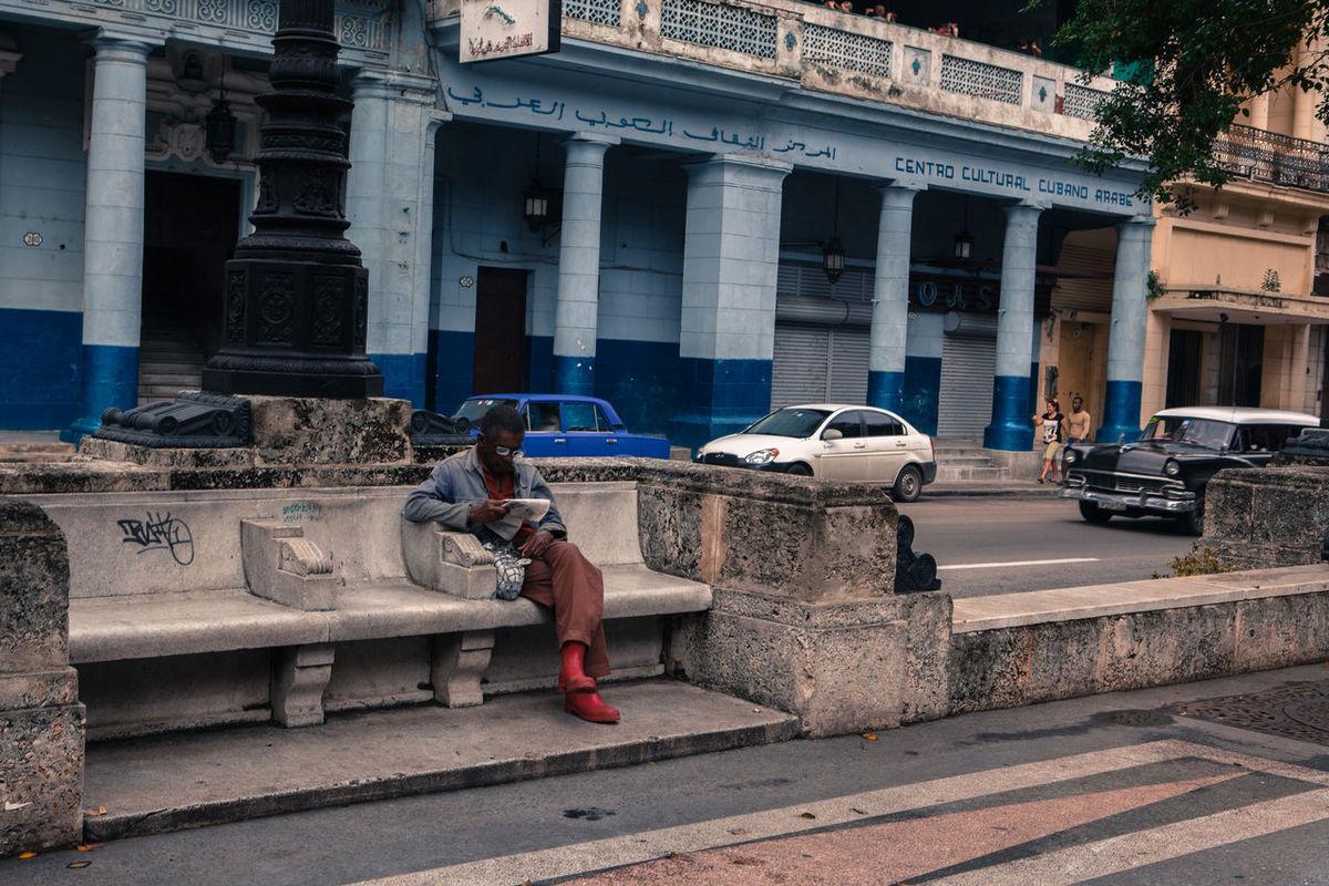 A man reads seated on a bench along Paseo Del Prado, Havana, Cuba. Bench Book Boulevard Breaktime Cuba Daily Life Havana Leisure Leisure Activity Man Paseo Del Prado Pillars Porch Promenade Read Stone