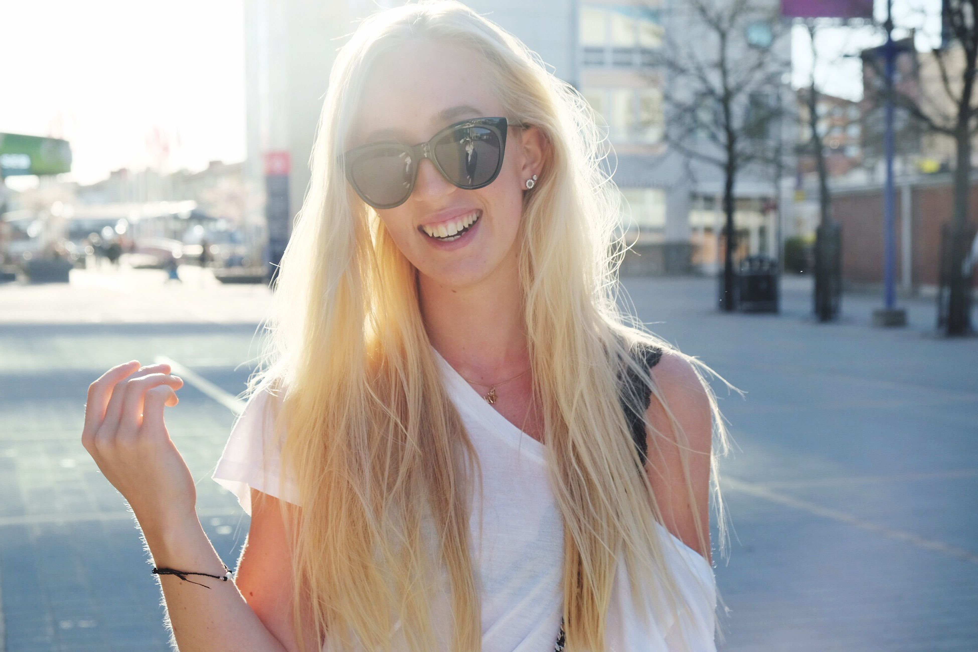 blond hair, smiling, one person, focus on foreground, young adult, beautiful woman, long hair, happiness, leisure activity, outdoors, young women, real people, front view, day, lifestyles, portrait, headshot, cheerful, women, eyeglasses, city, architecture, close-up, human lips, sky, adult, people