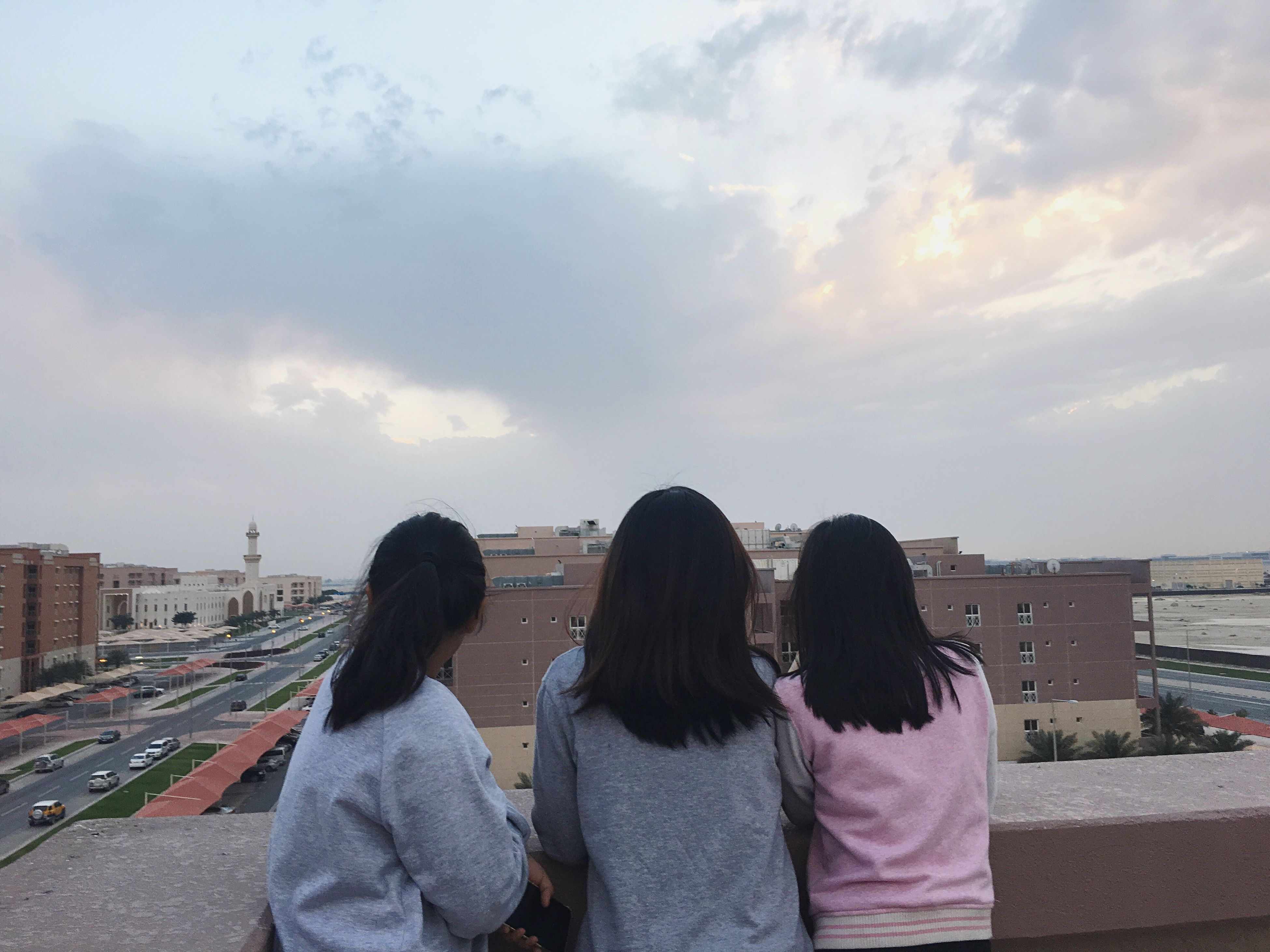 sky, togetherness, friendship, leisure activity, women, cloud - sky, real people, standing, built structure, bonding, people, building exterior, city, young women, outdoors, vacations, cityscape, adult, adults only, architecture, day, young adult