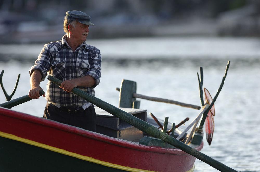 Greek Fisherman Adult Arms Boat Cap Checked Fisherman Greece Greek Hands Hat Man Moustache Nets Oar Oars One Person Outdoors Red Rowing Rudder Shirt Sunlight Tan Vessel Water