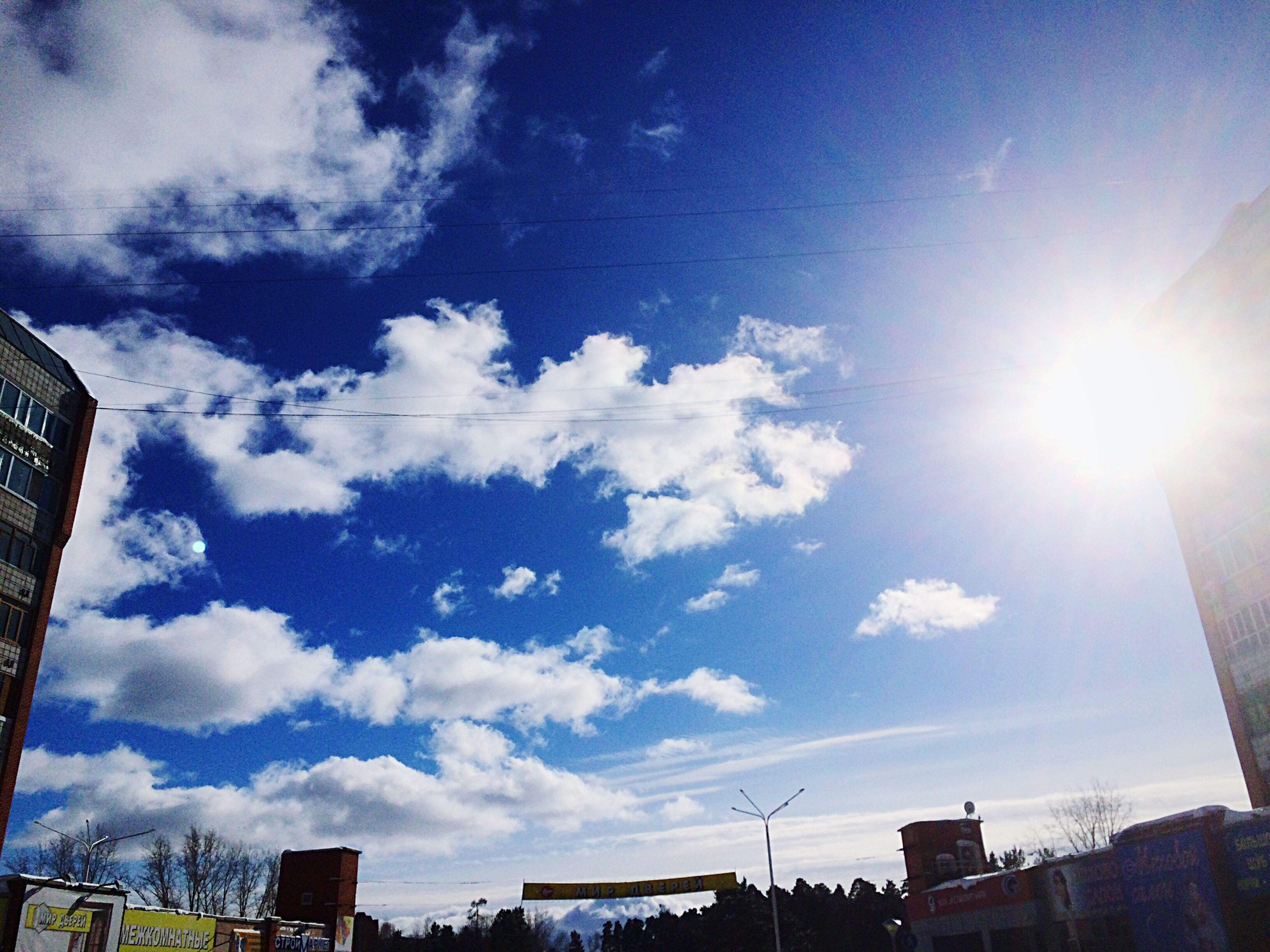building exterior, architecture, built structure, sun, sunbeam, low angle view, sky, sunlight, city, lens flare, cloud - sky, blue, sunny, building, cloud, bright, skyscraper, day, outdoors, vapor trail